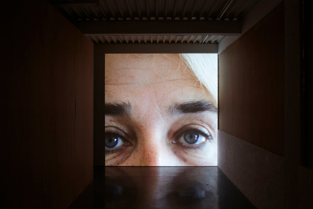 Video of the artists head projected onto a large wall.