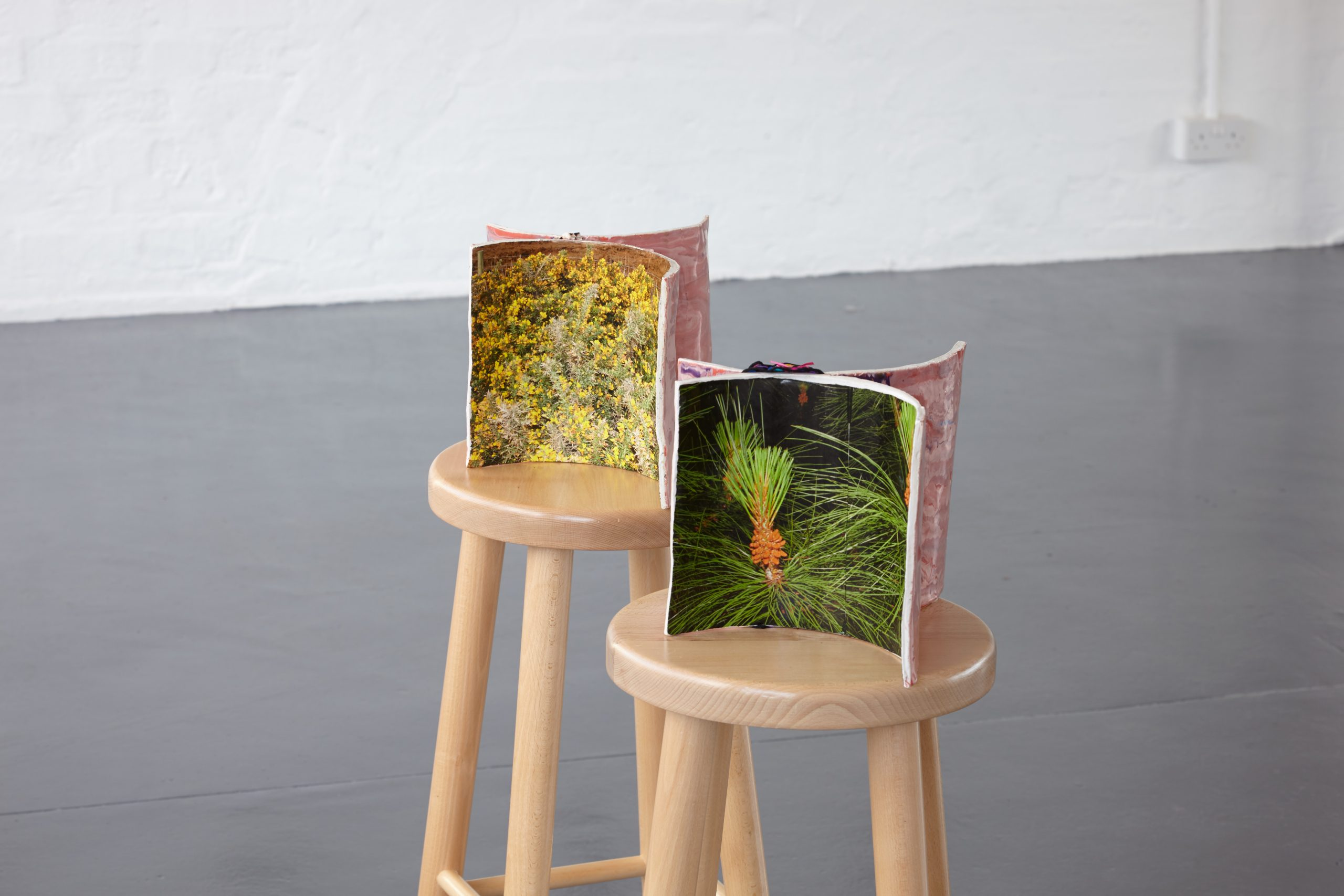 Two ceramic sculptures sit on stools.
