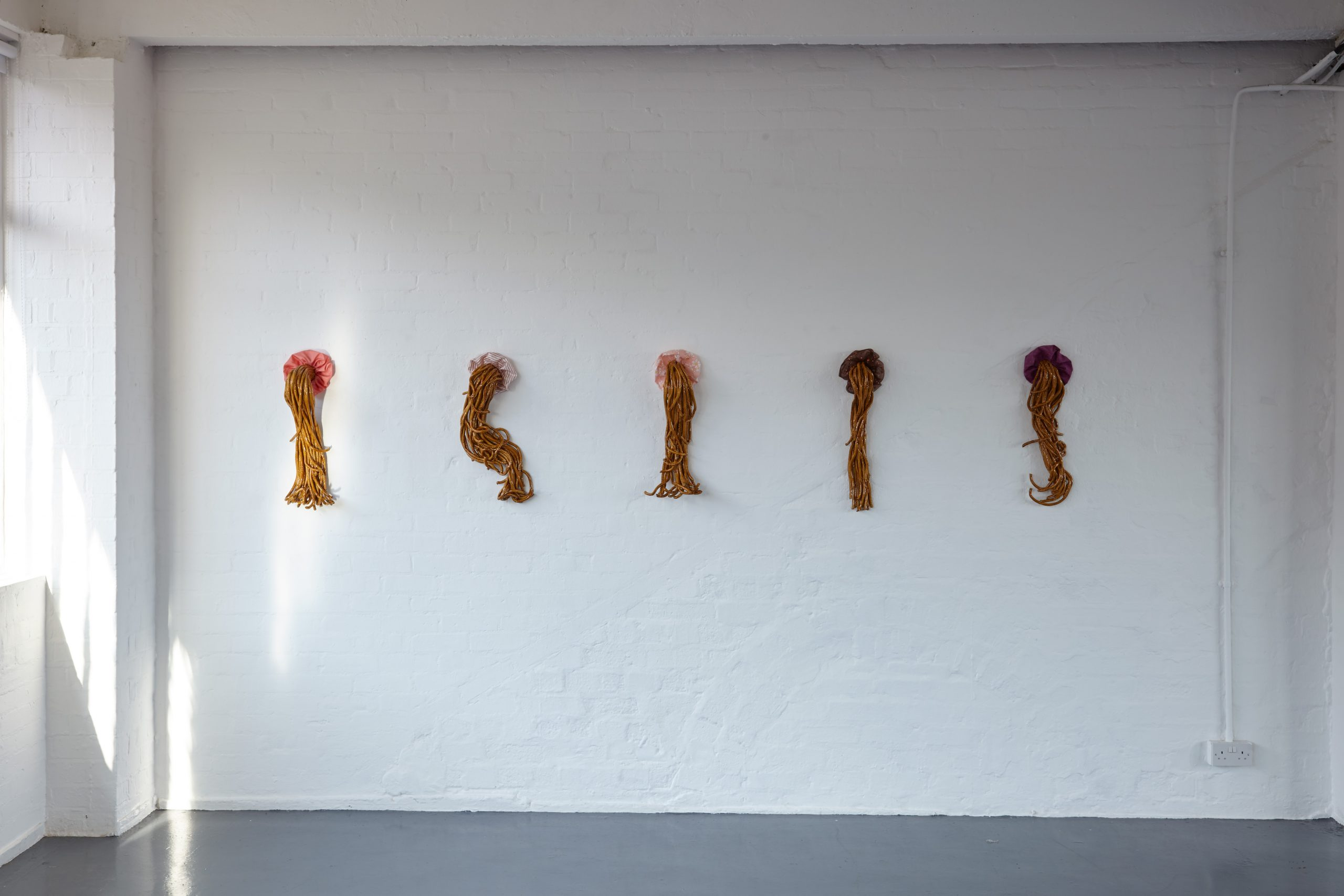 Ceramic ponytails with scrunchies hung on white wall.