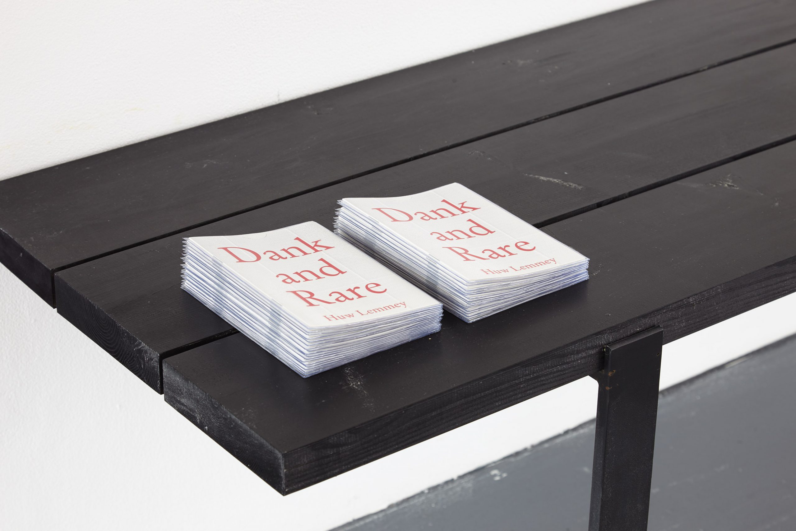 Two stacks of publications on a wooden bench.