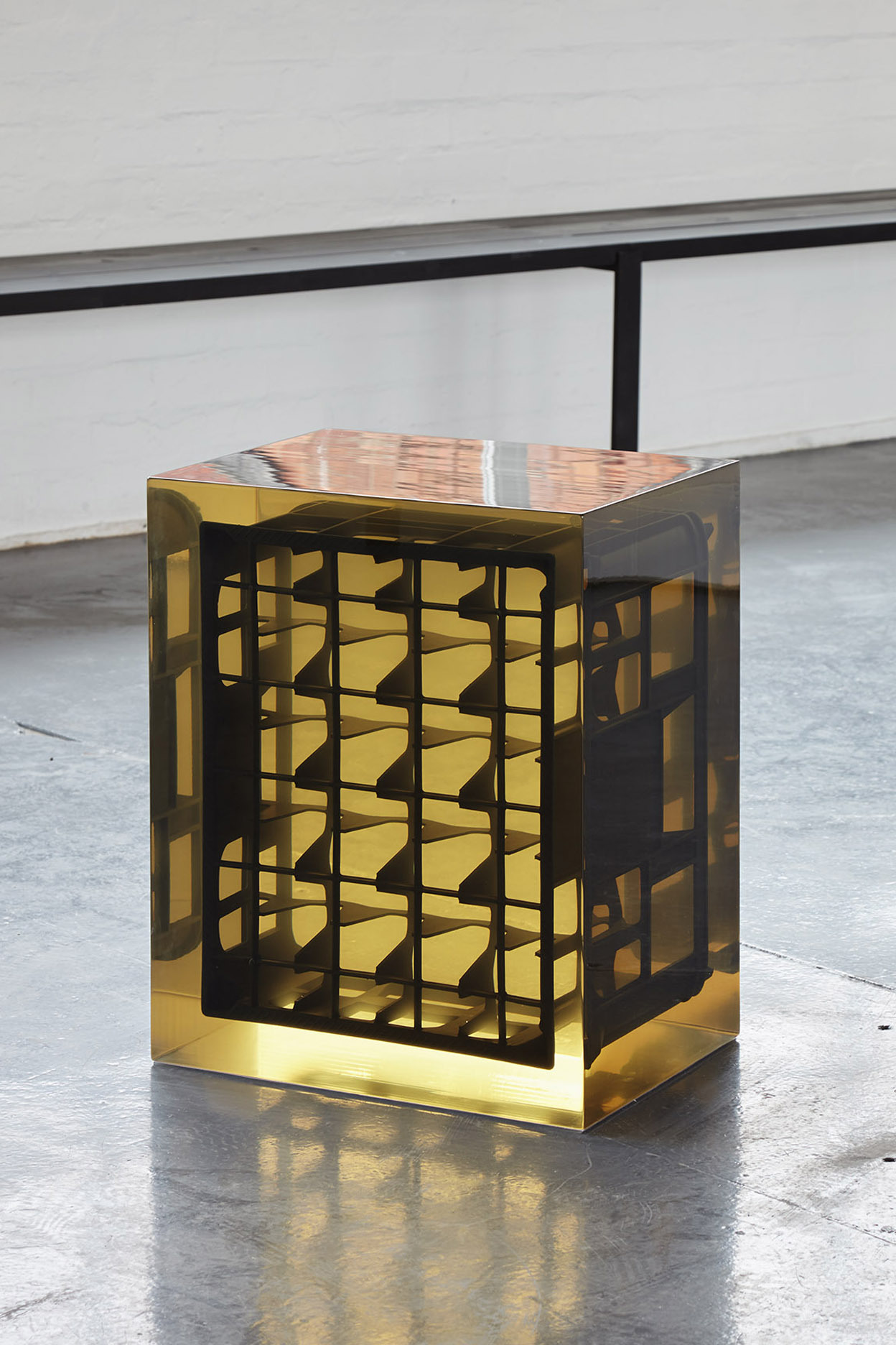 A beer crate suspended in golden resin.