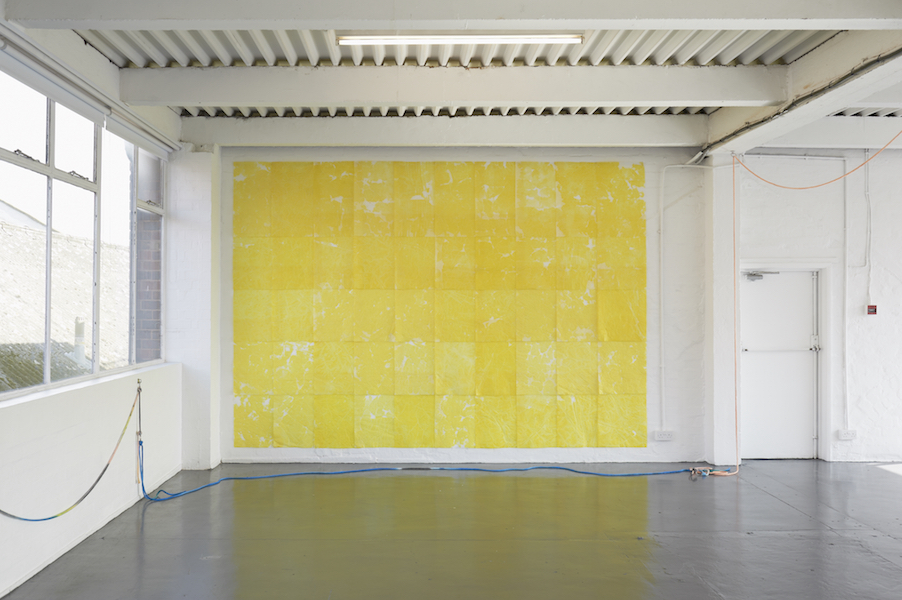 View of a wall hung with bright yellow tissue paper.