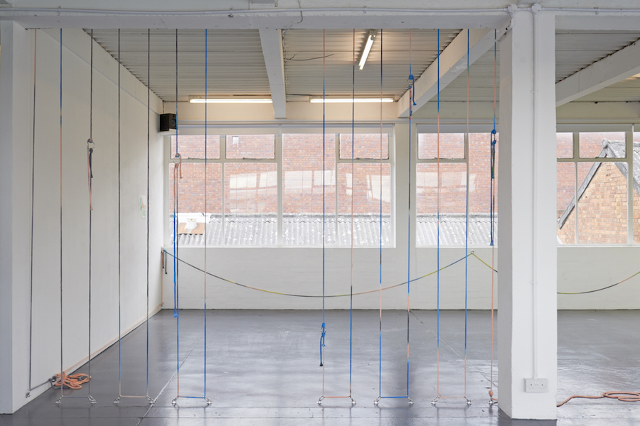 Painted coloured rope hung floor to ceiling in a line creating a barrier.