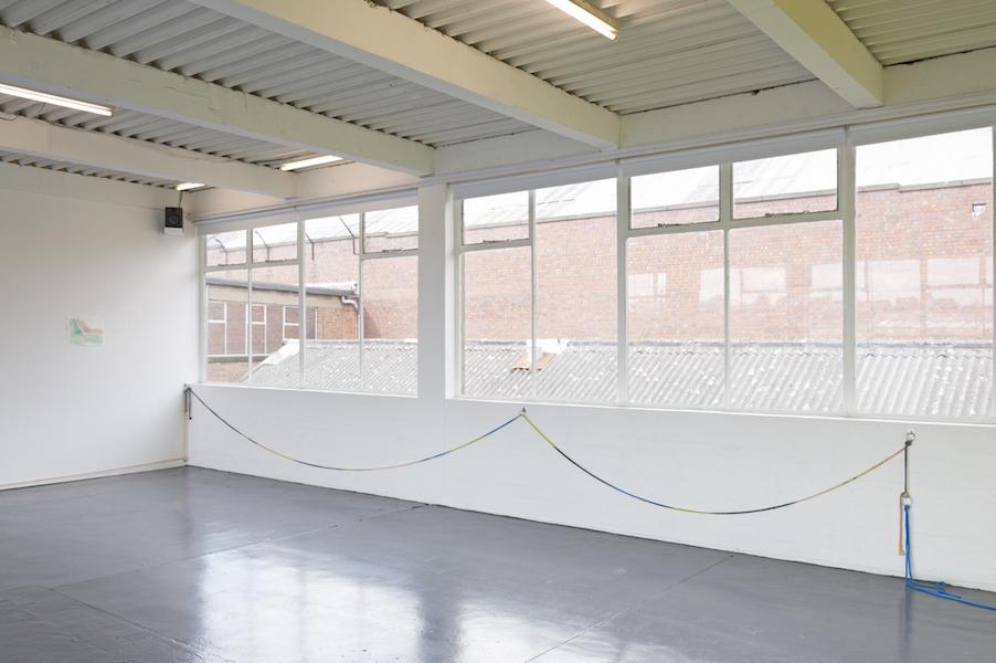 Painted rope looped across a brick wall below windows.
