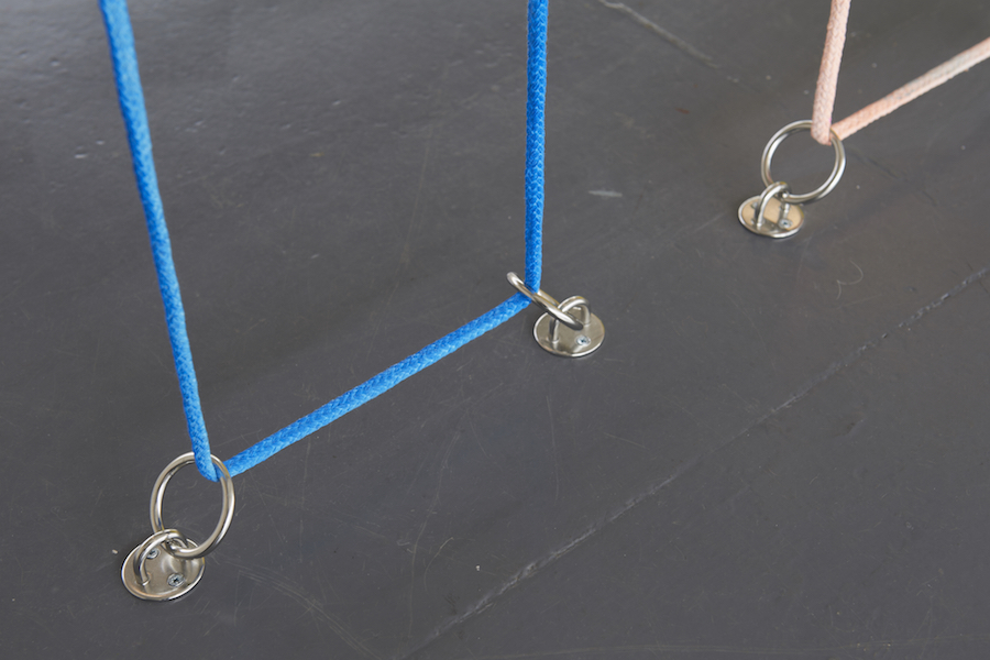 Close up of painted rope tethered to floor with metal loops.