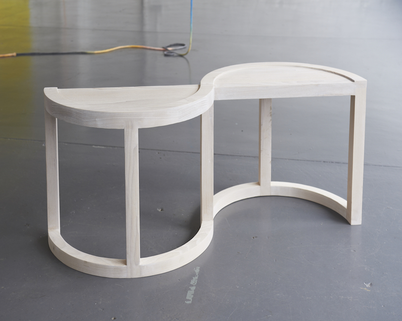 A small curved ash bench for two people.