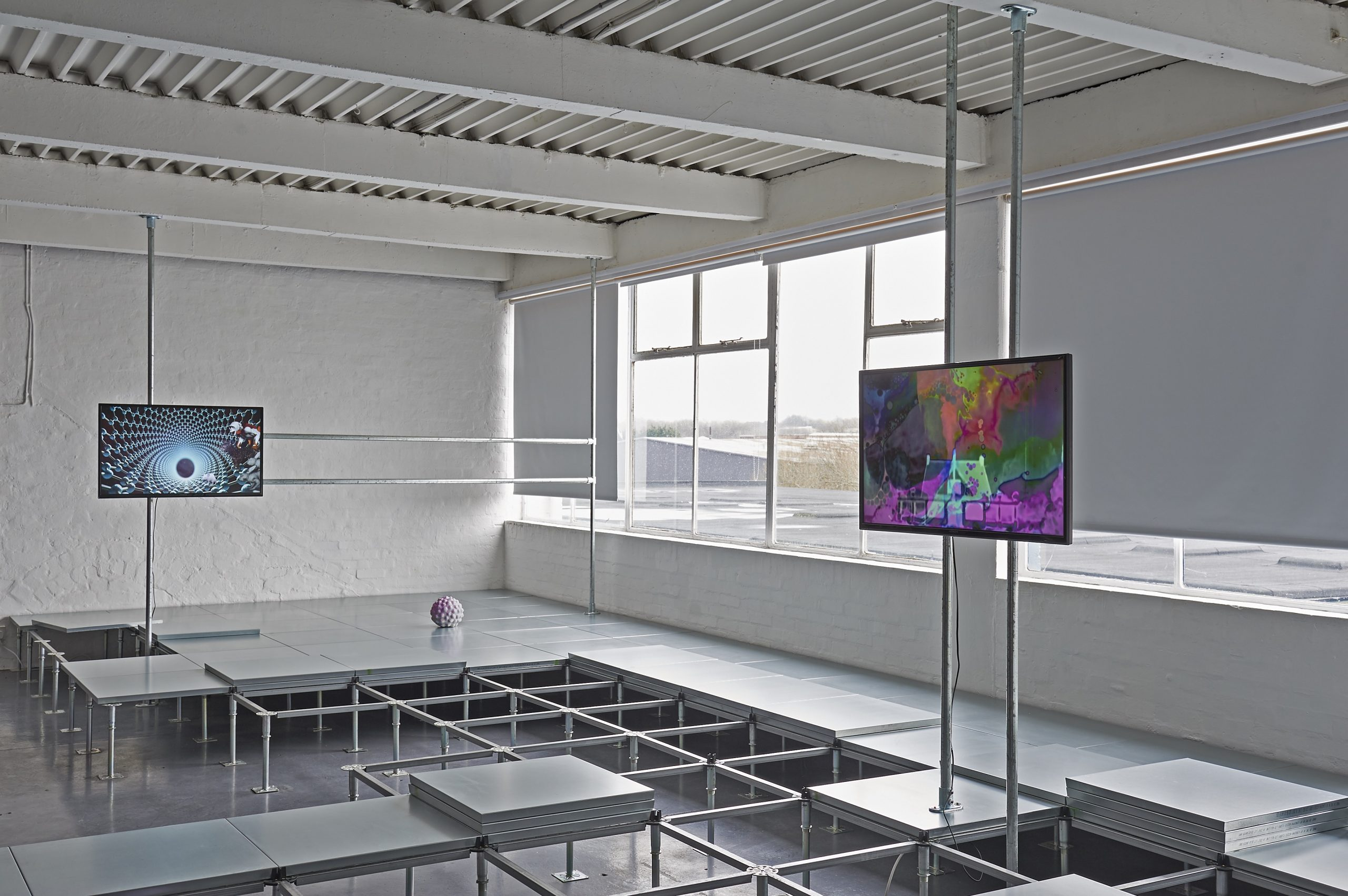 Metal squares form a raised platform across the floor. Videos are showing on two TVs mounted above on scaffold.