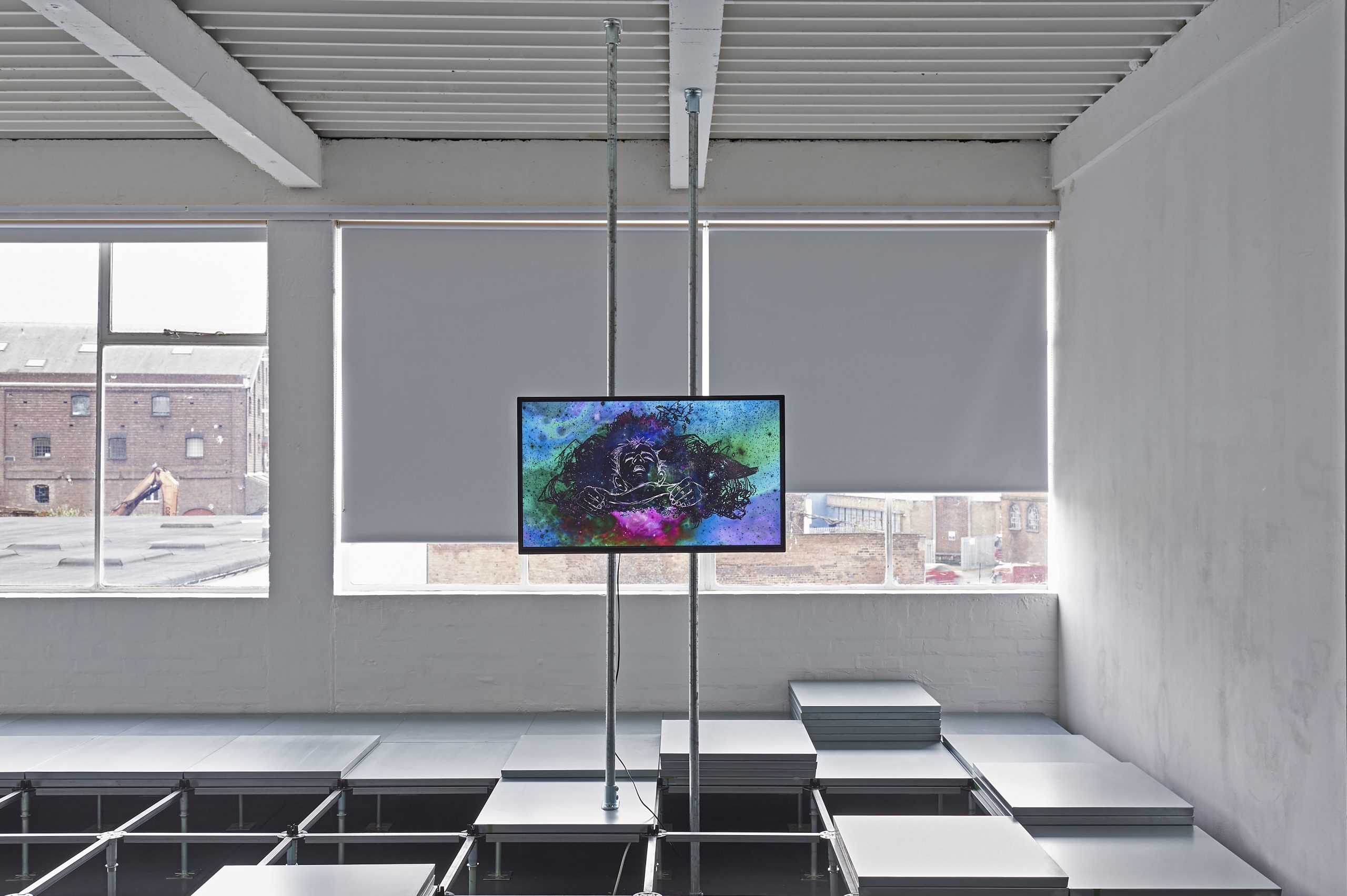 Metal squares form a raised platform across the floor. A video is showing on a tv mounted above on scaffold.