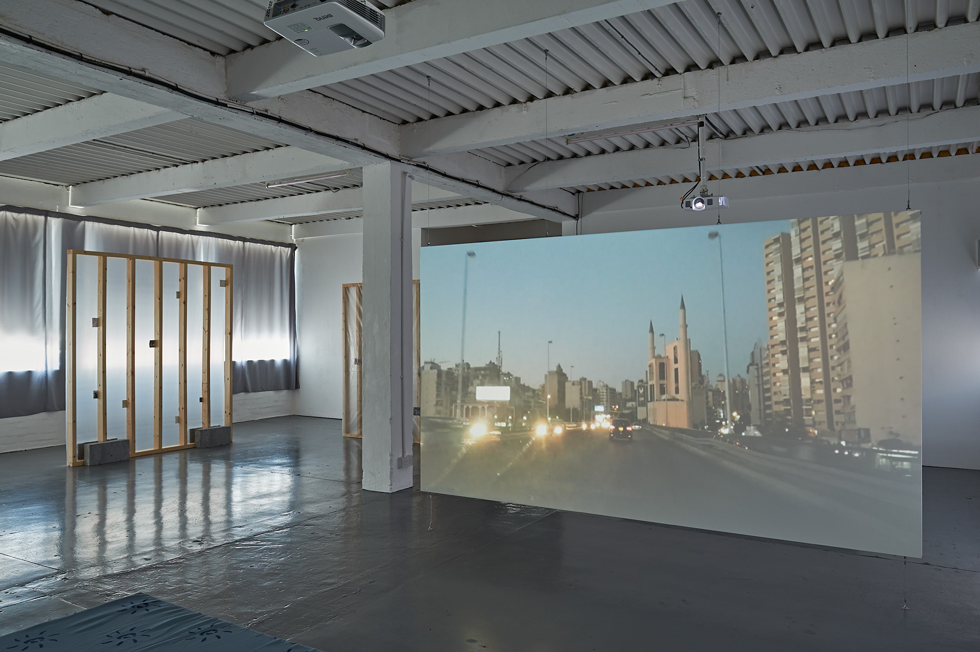 A custom made wooden projection screen hangs from the ceiling onto which a video is projected, a wall like structure covered in translucent plastic sits in the background.