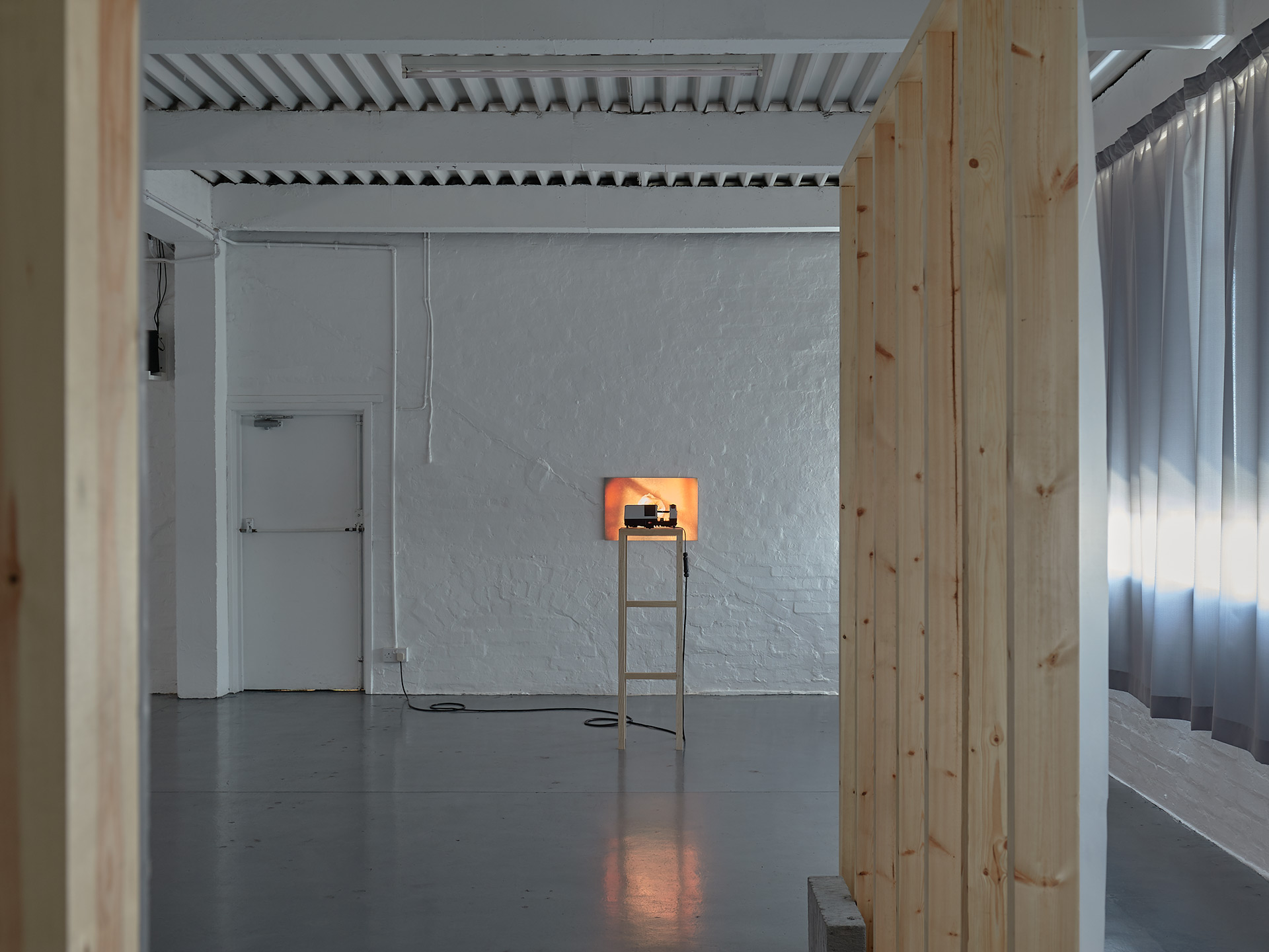 Two wooden wall like structures are seen from a side angle, in the background a slide projector sits on a custom made wooden plinth projecting a single image of a bag of fruit. There is a grey curtain to the right of the image.