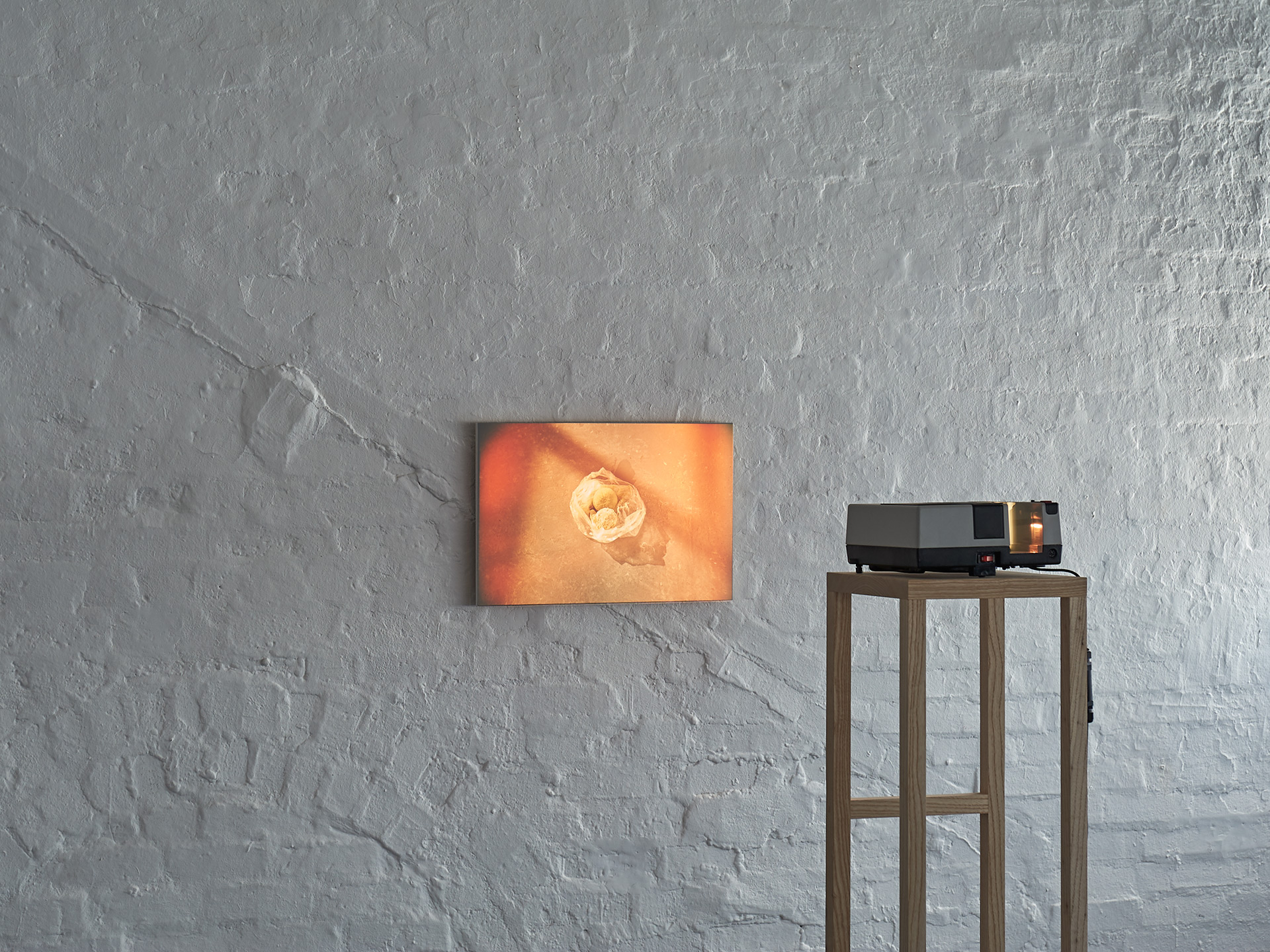 A slide projector sits on a custom made wooden plinth. It projects a single image of some soft fruit in a bag. The image is sepia and orange in tone.