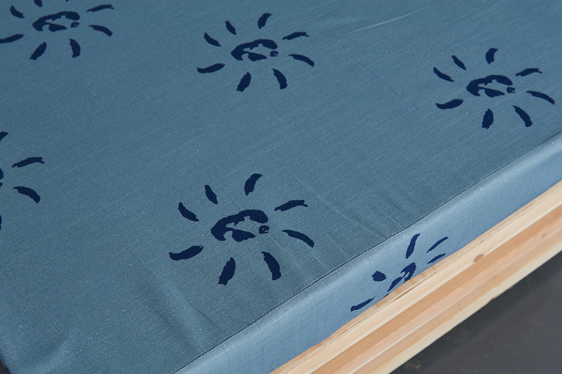 A close up of a custom made seating platform with a light blue textile with dark blue sun like patterns.