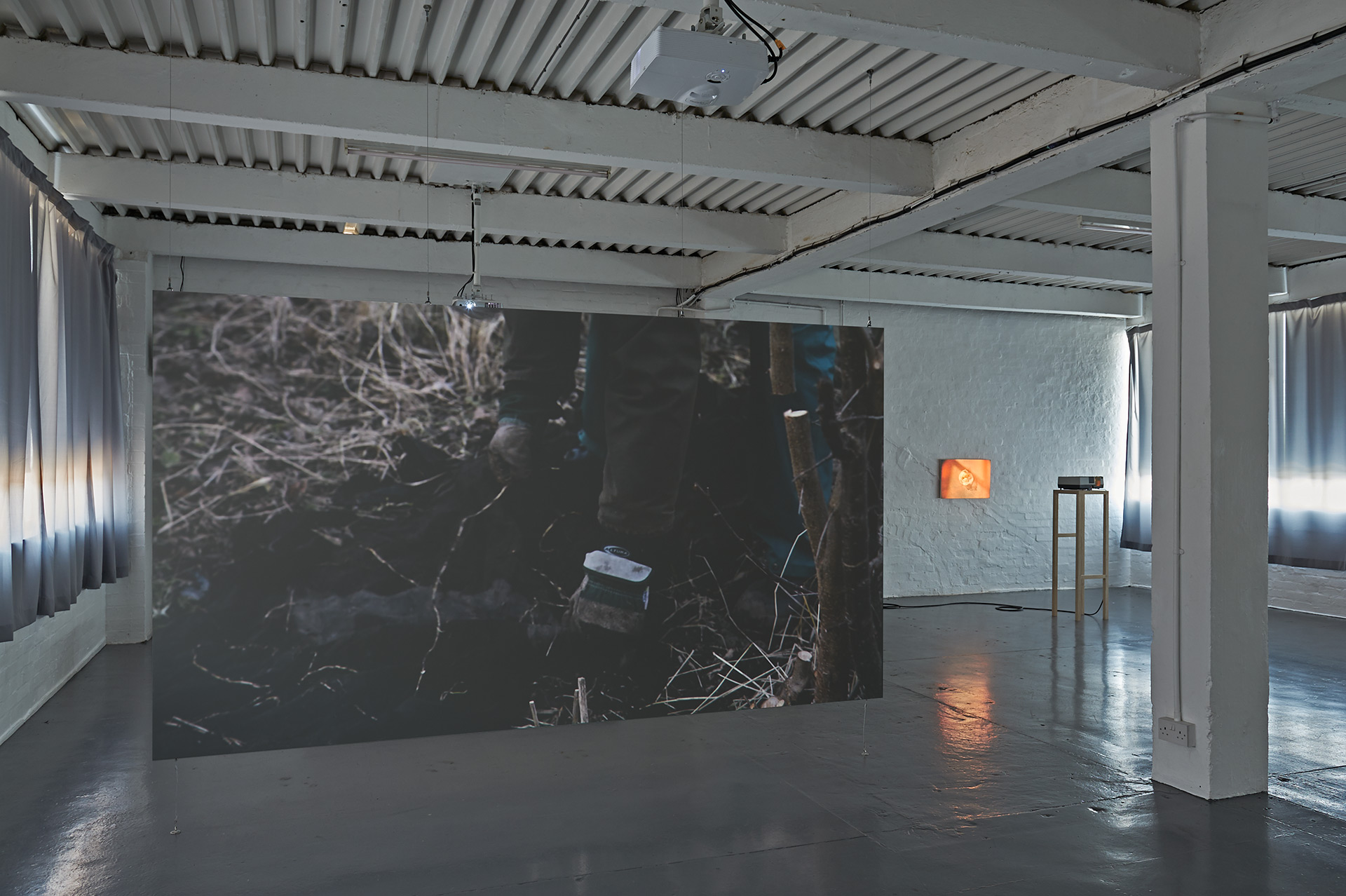 A custom made wooden projection screen hangs from the ceiling onto which a video is projected, in the background a slide projector sits on a custom made wooden plinth projecting a single image of a bag of fruit.