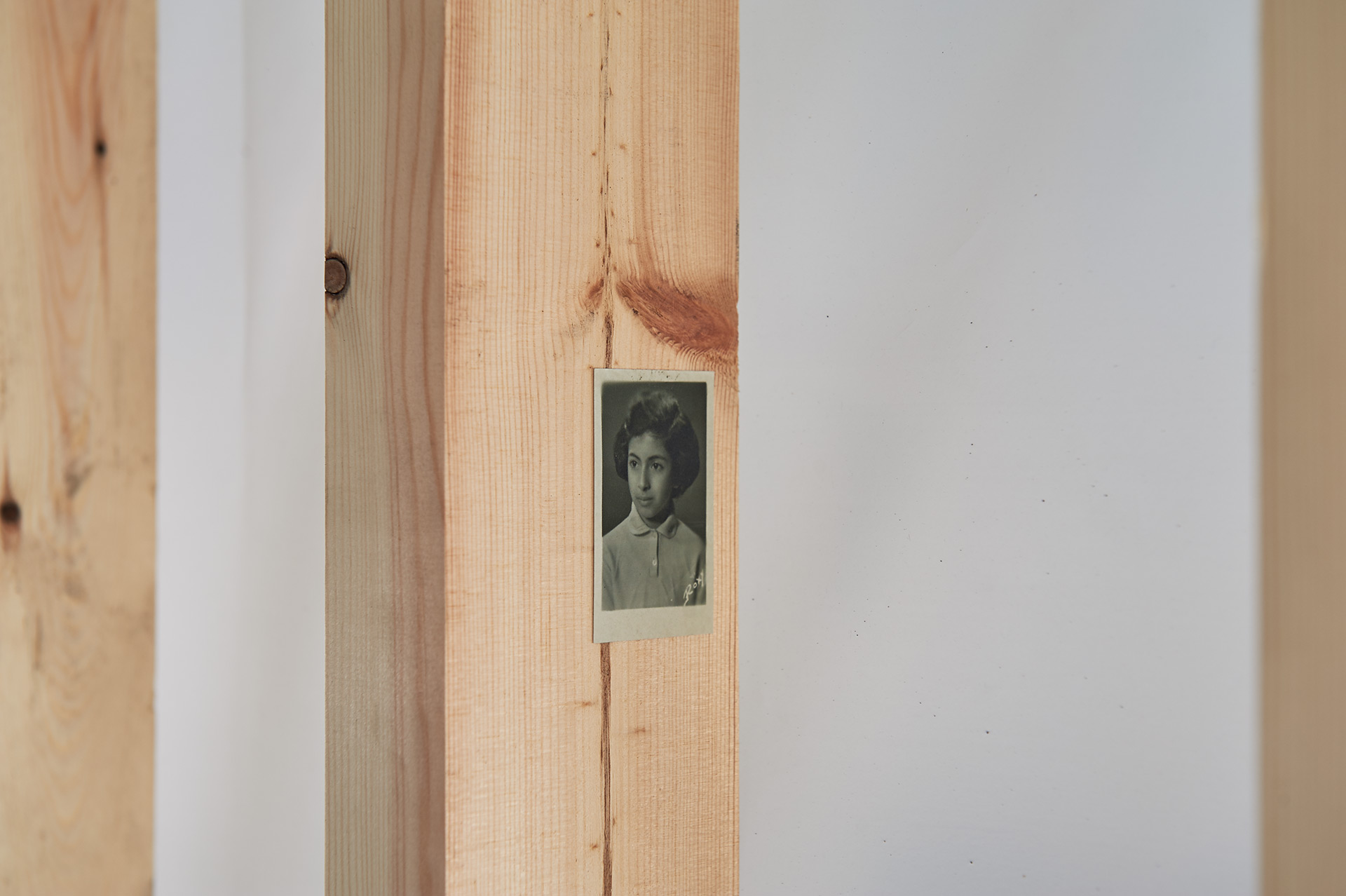 Close up of a wooden wall structure covered with translucent plastic. A small old portrait style photograph of a young child can be seen attached to the wood.