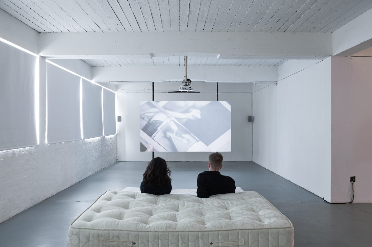 Two people sit on mattresses in a gallery watching a video on a custom made projector screen.