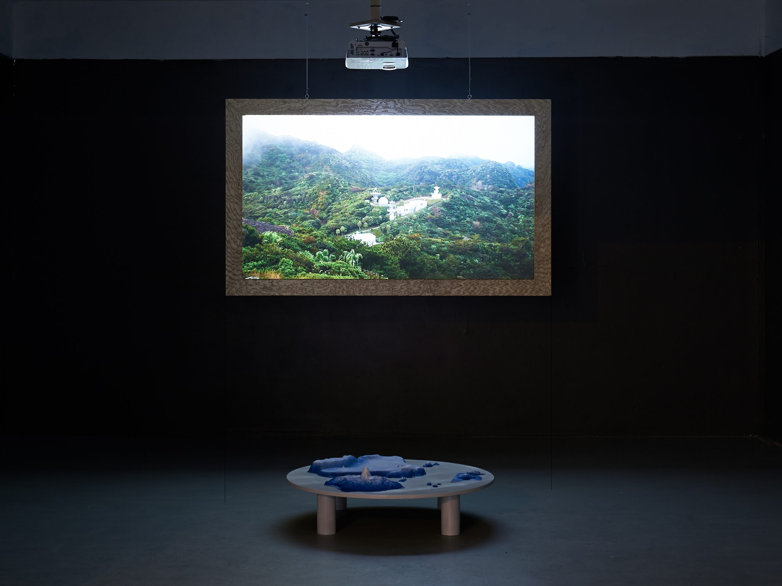 In a dark space a film is projected on to a wall, on the floor a small round table with a model on it is in the foreground.