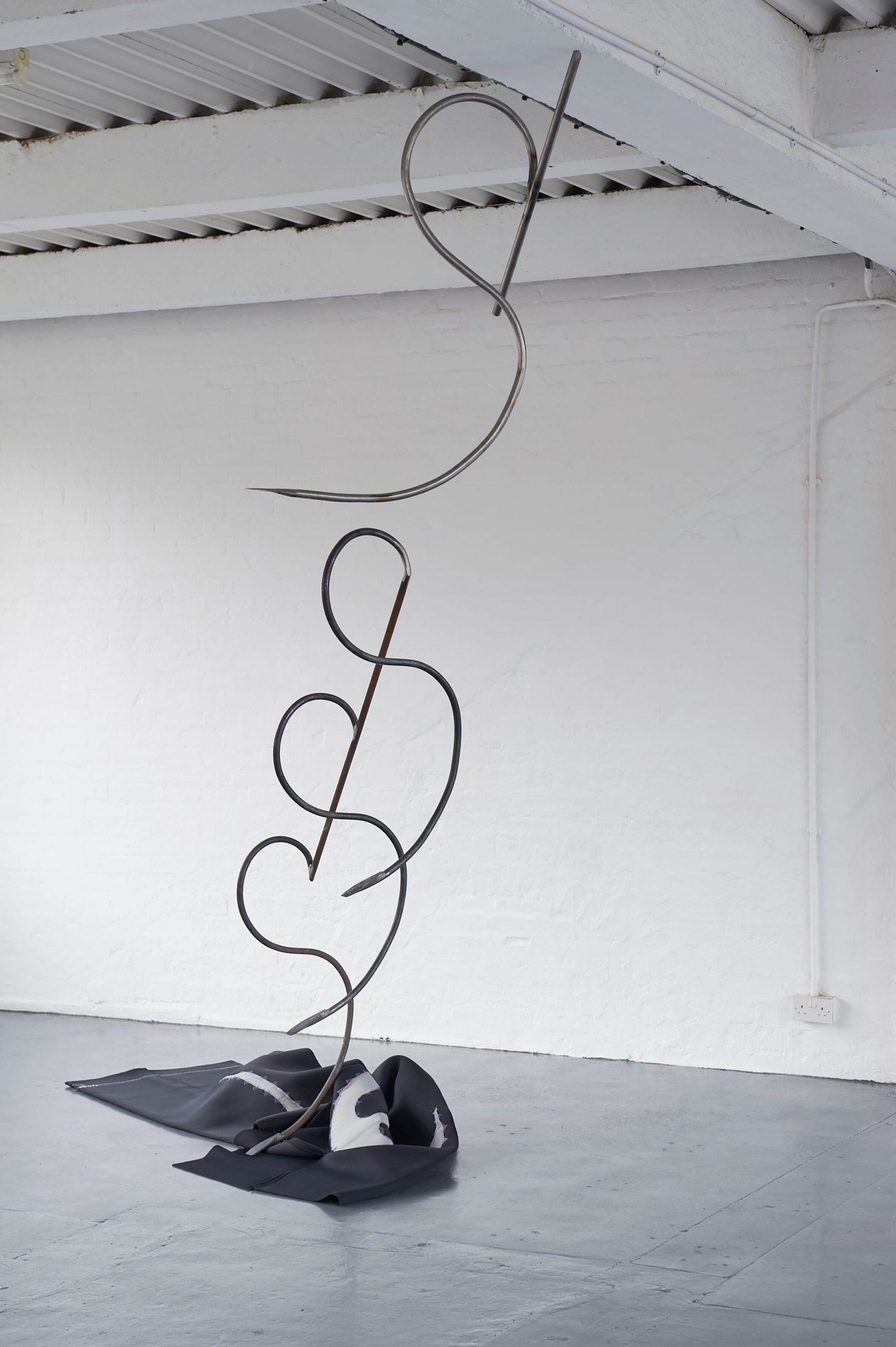A piece of black neoprene lies on the ground, out of this rises a steel spiral sculpture that reaches towards the ceiling.
