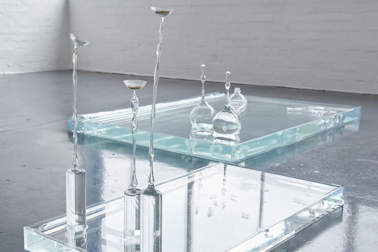 Blown glass objects sit in two shallow vitrines filled with water.