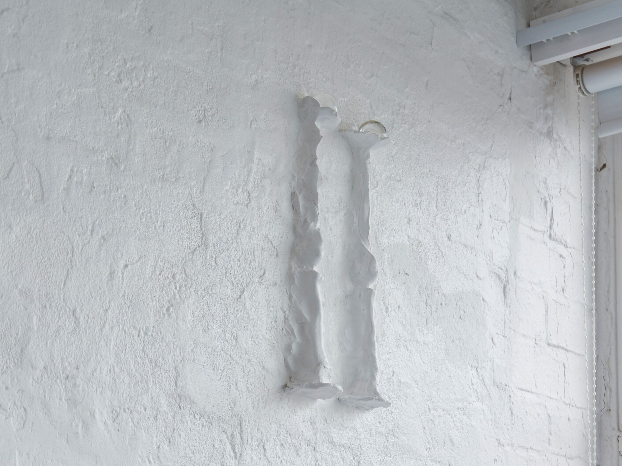 Two thin white column shaped objects hang high on a white gallery wall.