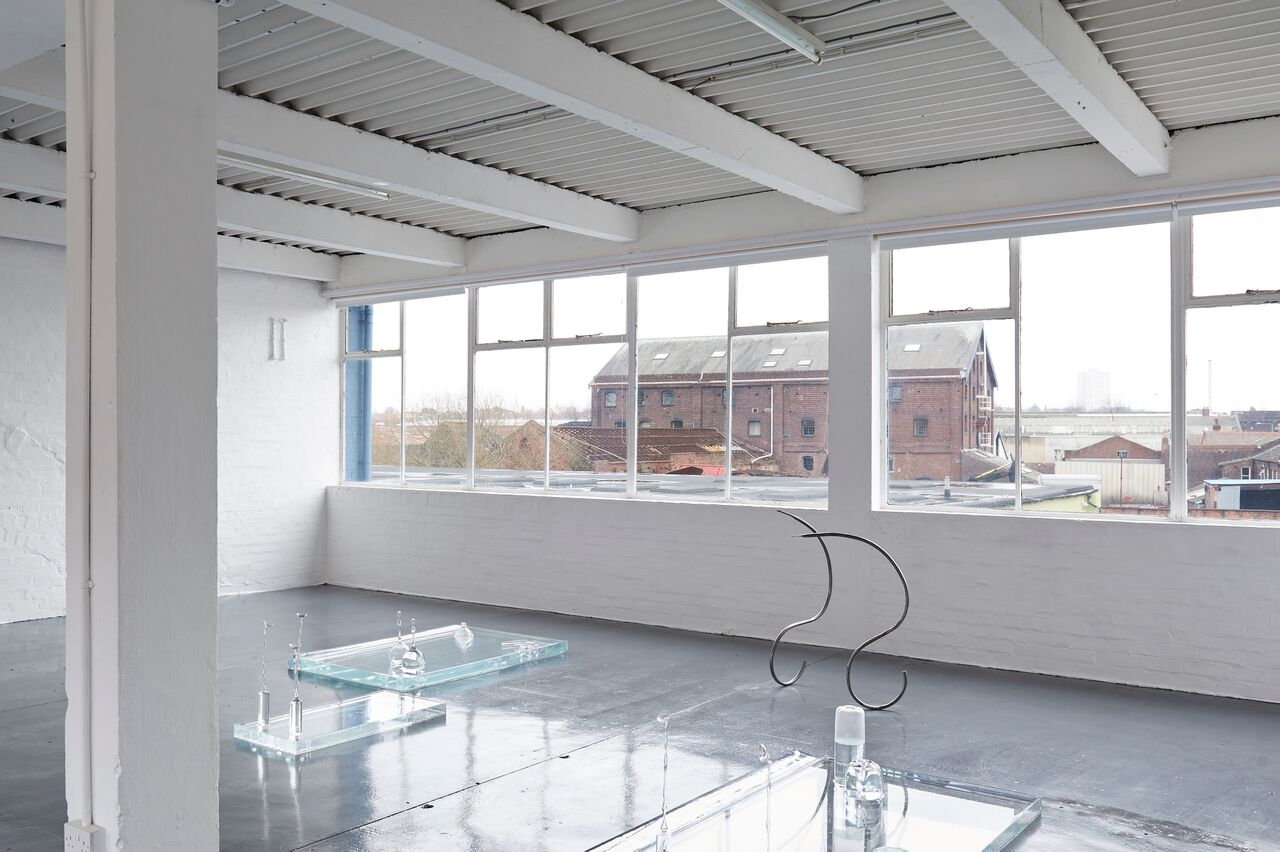 A wide shot of a white gallery space with windows in the background. On the ground are three shallow vitrines filled with water with glass objects standing in them. Two elegant