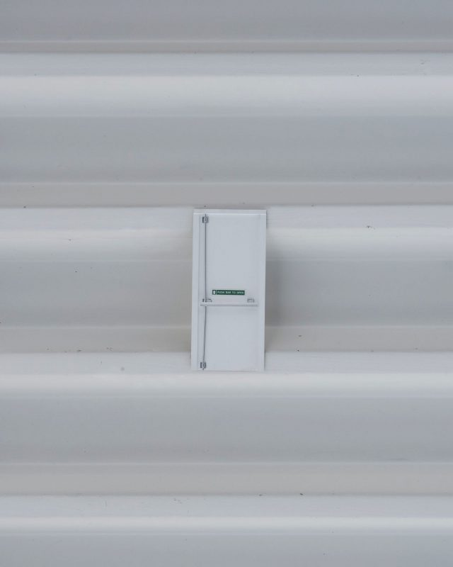 A miniature fire exit door affixed to a white gallery ceiling.
