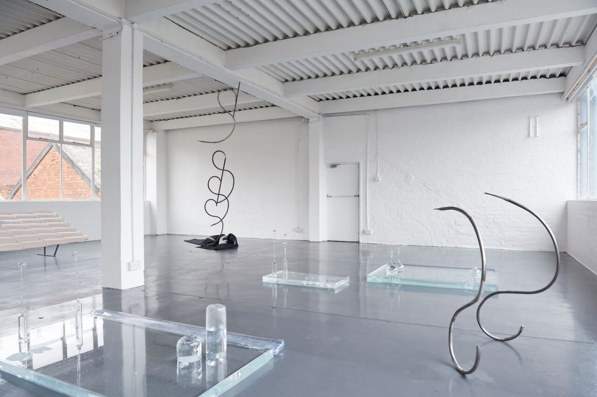 """Wide exhibition view three vitrines filled with water are scattered across the floor, two """"s"""" shaped steel sculptures rise from the floor."""