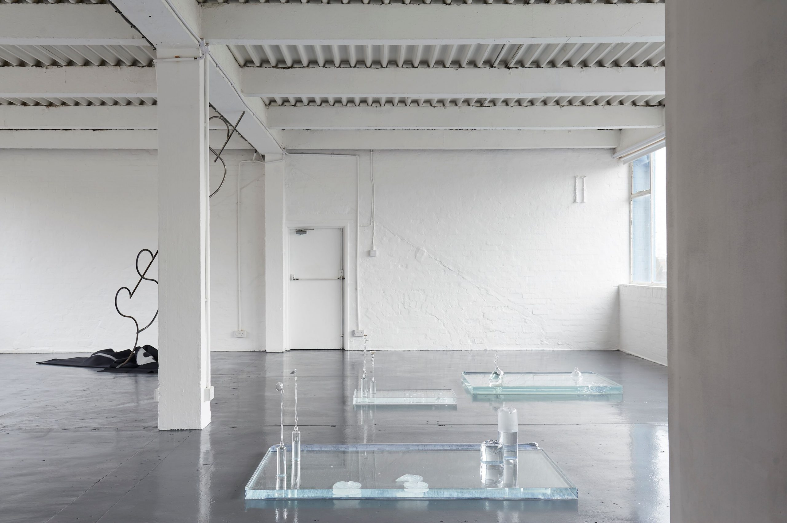 Wide exhibition view three vitrines filled with water are scattered across the floor, two