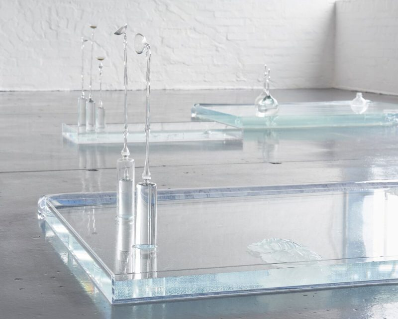 Blown glass objects and vessels sit in three shallow vitrines of different sizes filled with water lie on the floor.