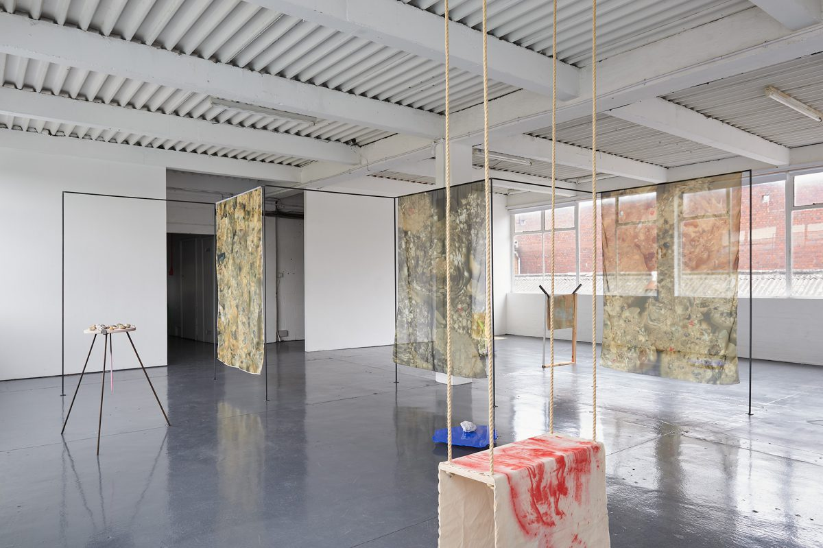 A wide exhibition view in which a variety of sculptures and structures can be seen. A swing draped with canvas is in the foreground, in the background a steel frame cuts across the gallery, a printed mesh curtain hangs from this.