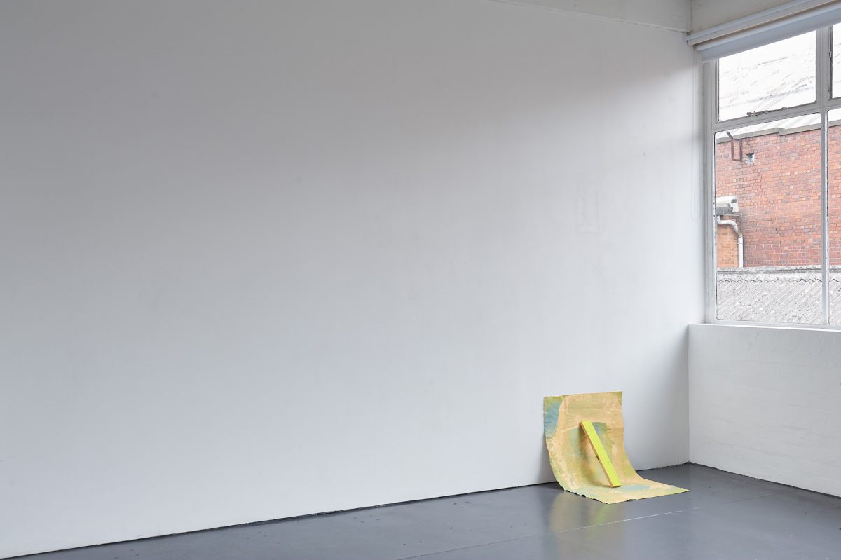 An abstractly painted piece of canvas is propped against a white wall with small green piece of wood.