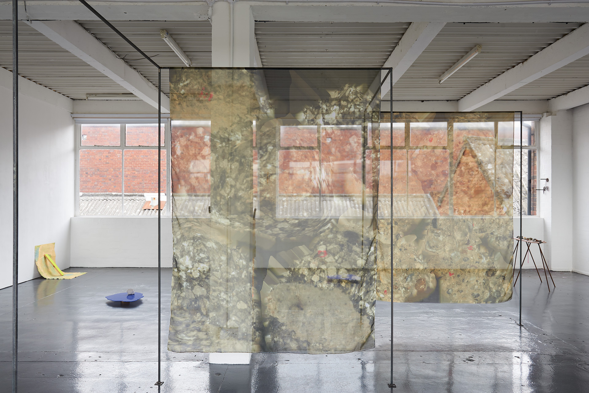 A thin steel frame structure cuts through the gallery, a mesh curtain hangs from the structure, printed with images of rock like forms.