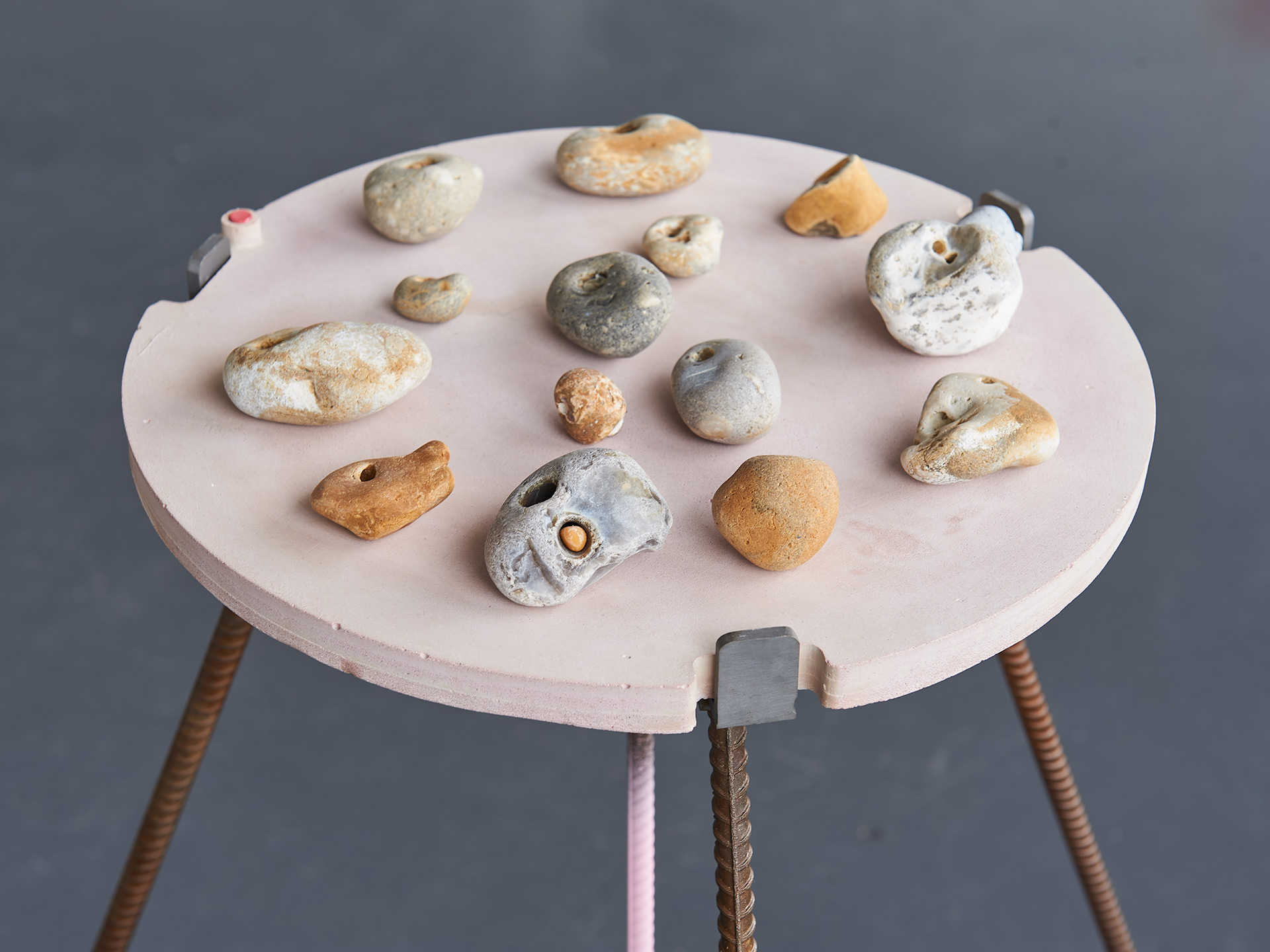 A series of small sculptures made of stacked jesmonite and stones are placed on top of a custom made circular table like plinth. Painted pale pink with steel rod legs.