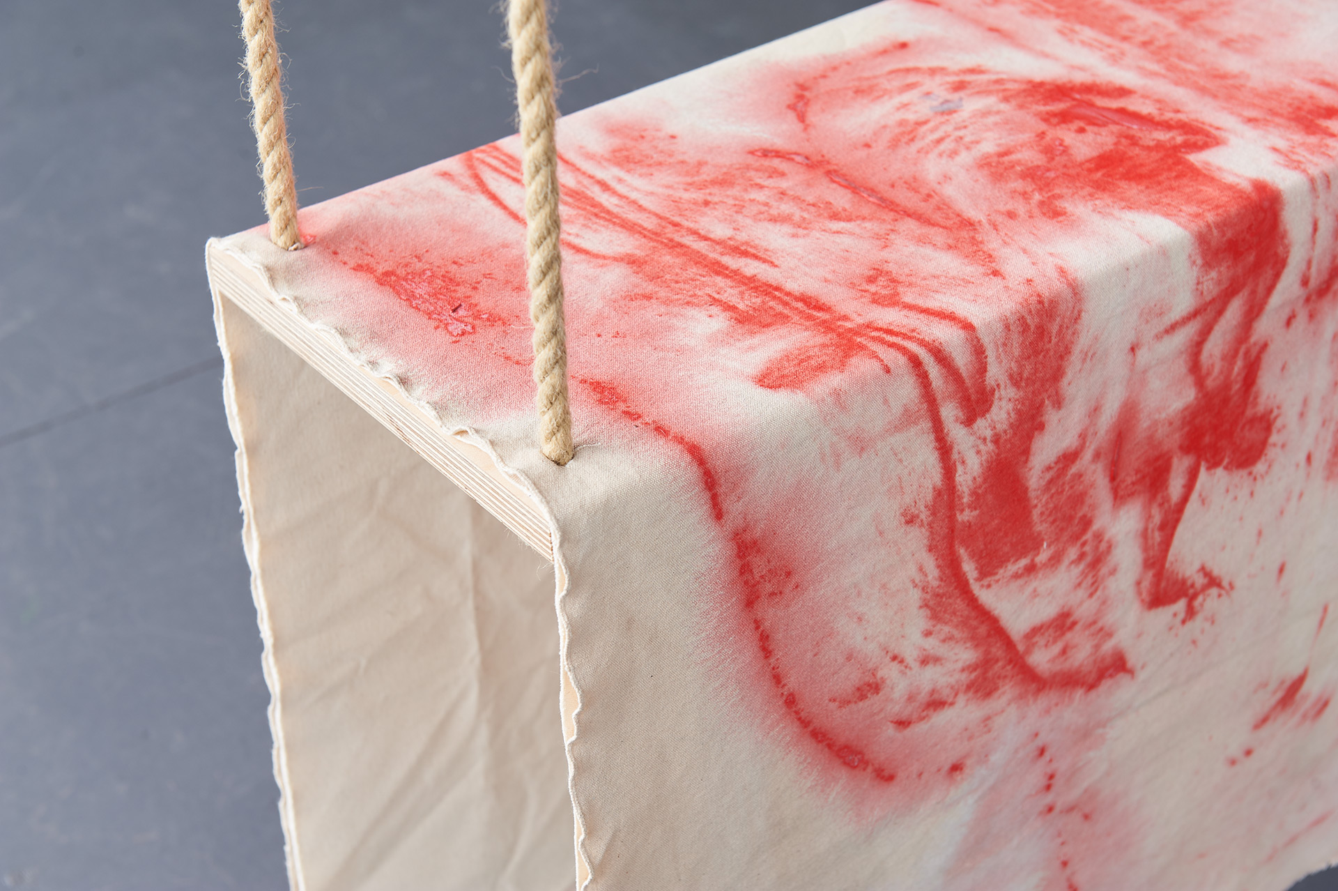 Close up view of the corner of a swing with a piece of canvas with red paint is draped over the seat.