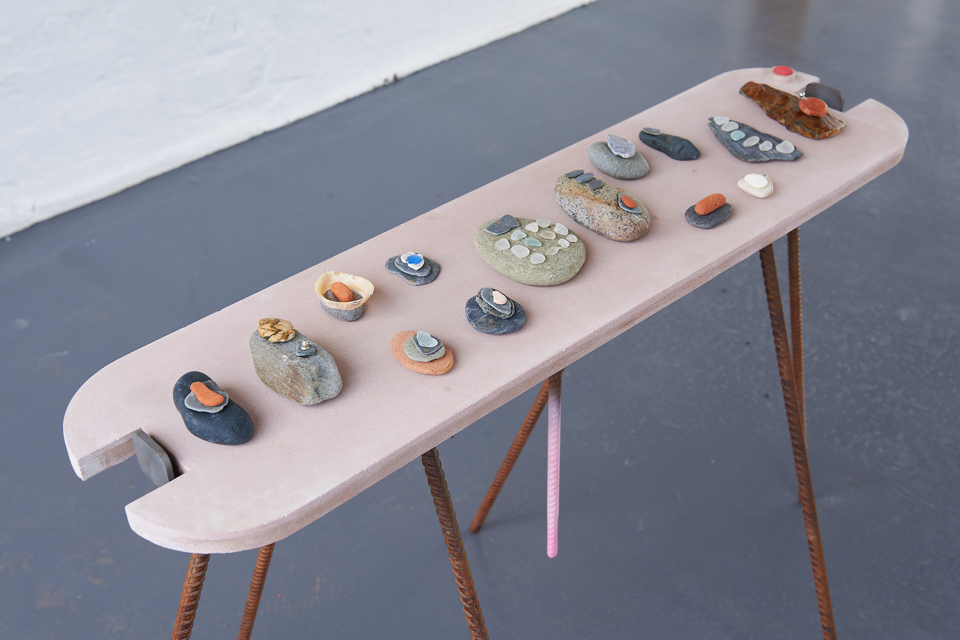 A series of small sculptures made of stacked jesmonite and stones are placed on top of a custom made table like plinth. Painted pale pink with steel rod legs.