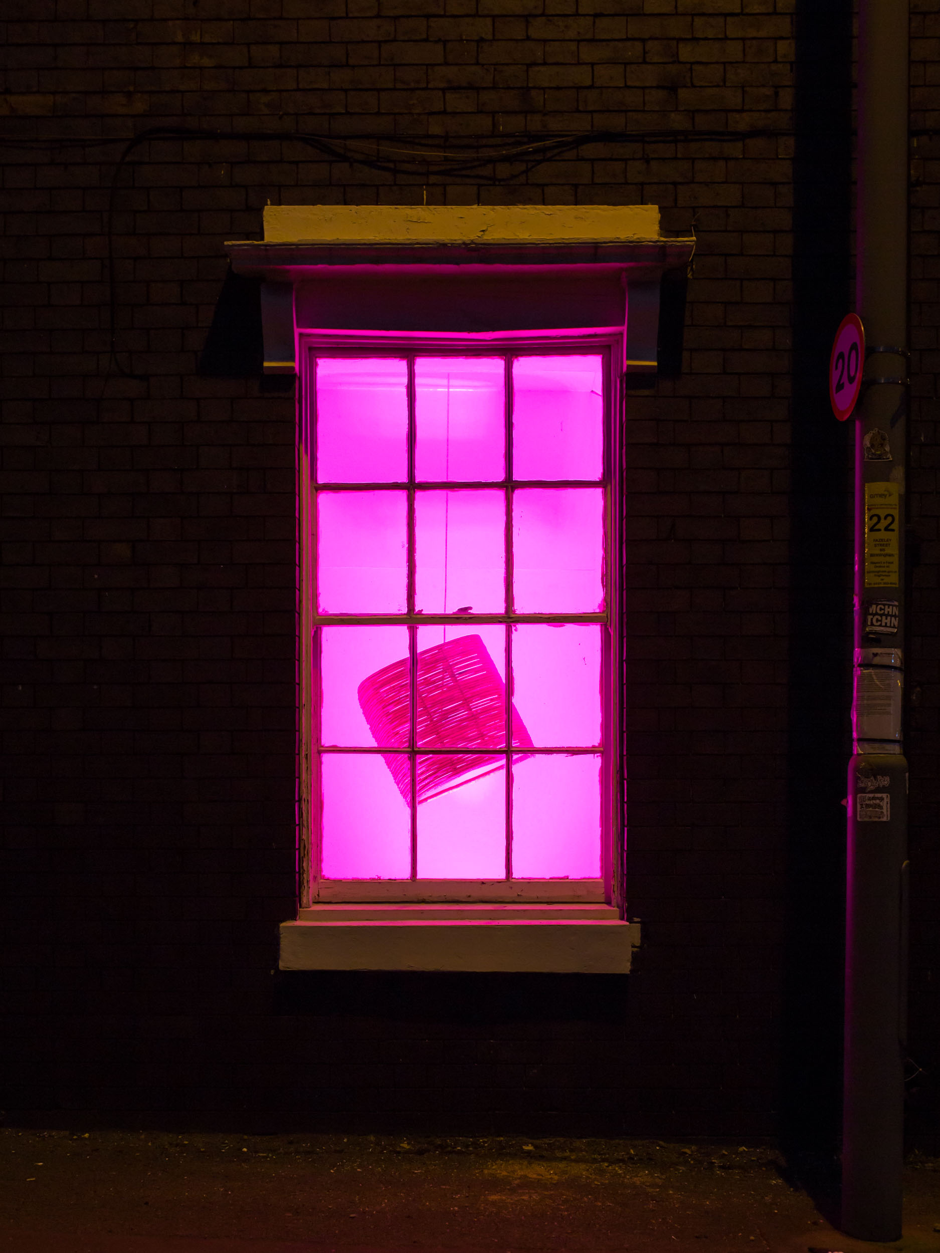 A lantana stool hanging in a pink lit window