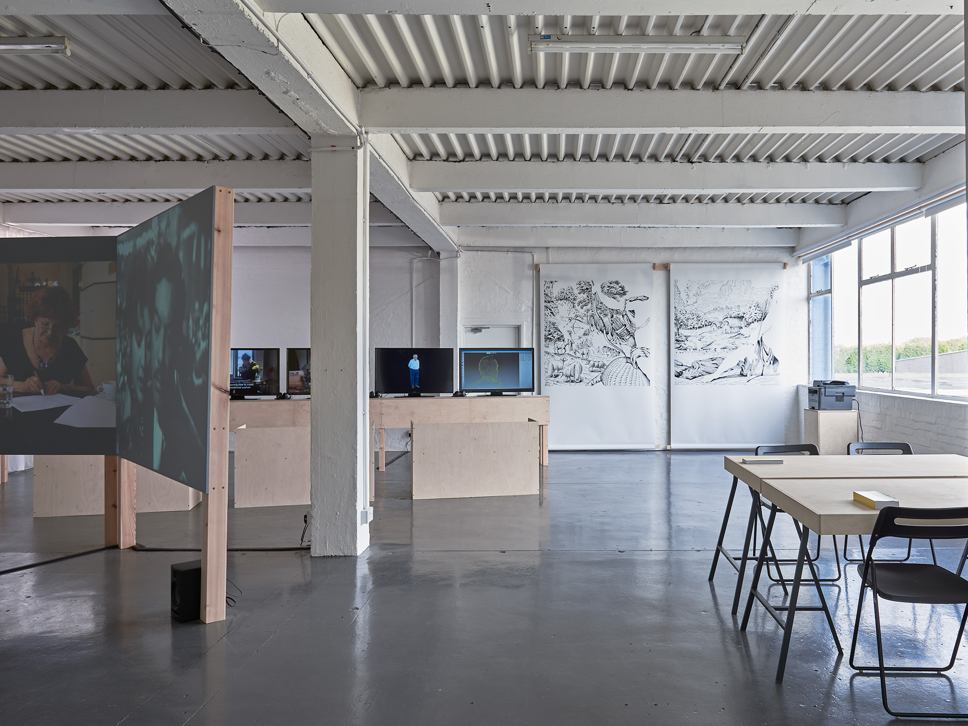 A wide shot of the gallery space, a set of chairs and a table can be seen to the right, a custom made projector screen to the left. In the background a series of TVs on a custom made plinth and two drawings hung on a brick wall beyond.