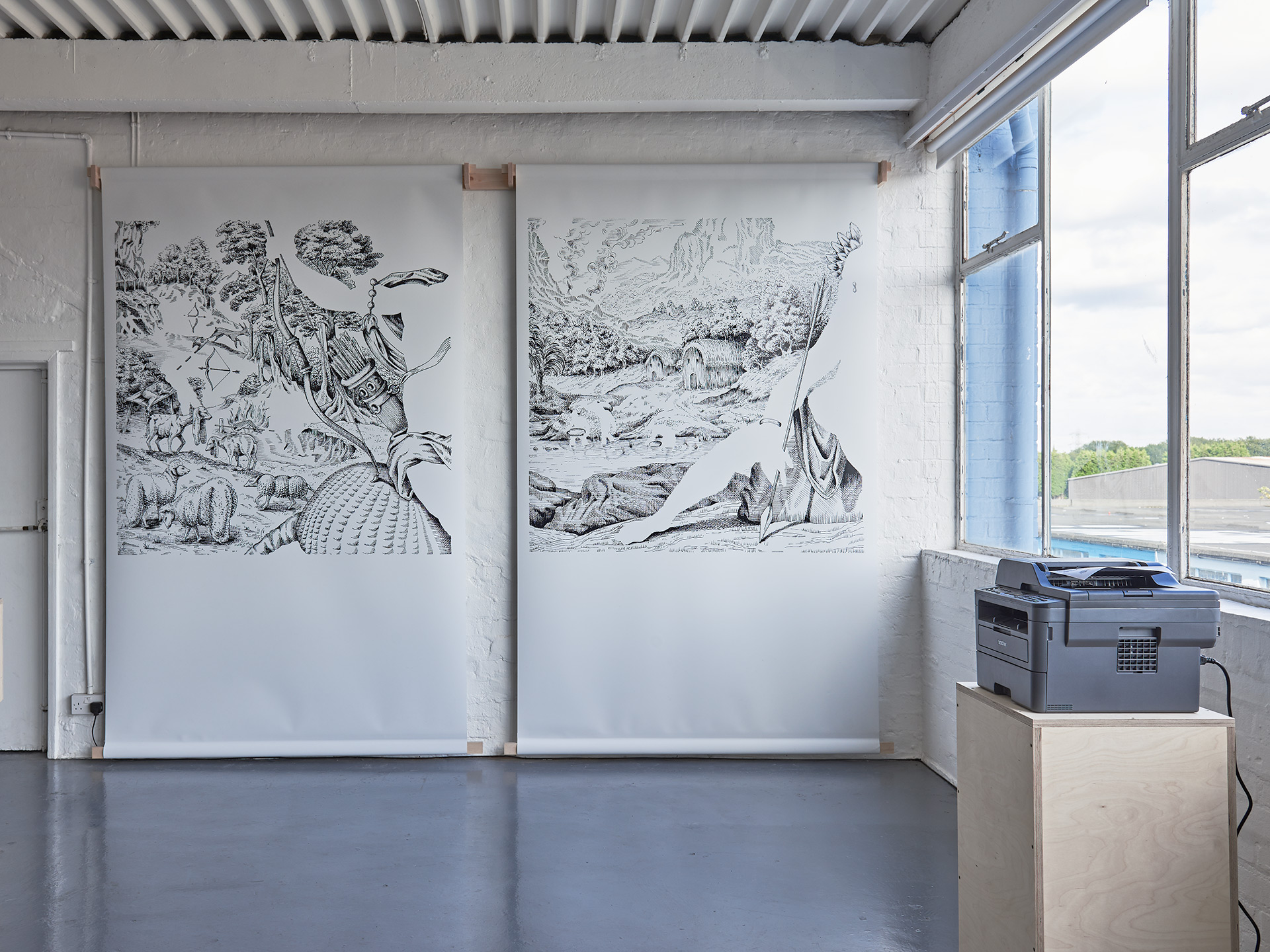 Two large printed drawings hang from a white brick wall, a printer on a plinth can be seen in the foreground.
