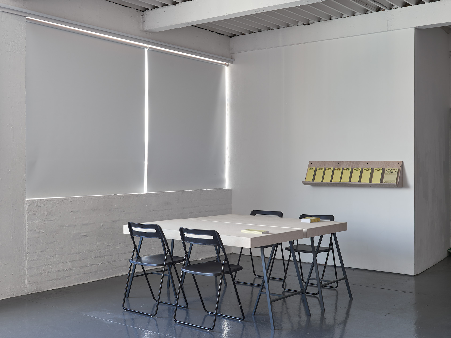A custom made table is place in the corner of the gallery with four black chairs around it, on the wall behind a stack of yellow publications sit on a custom made shelf.