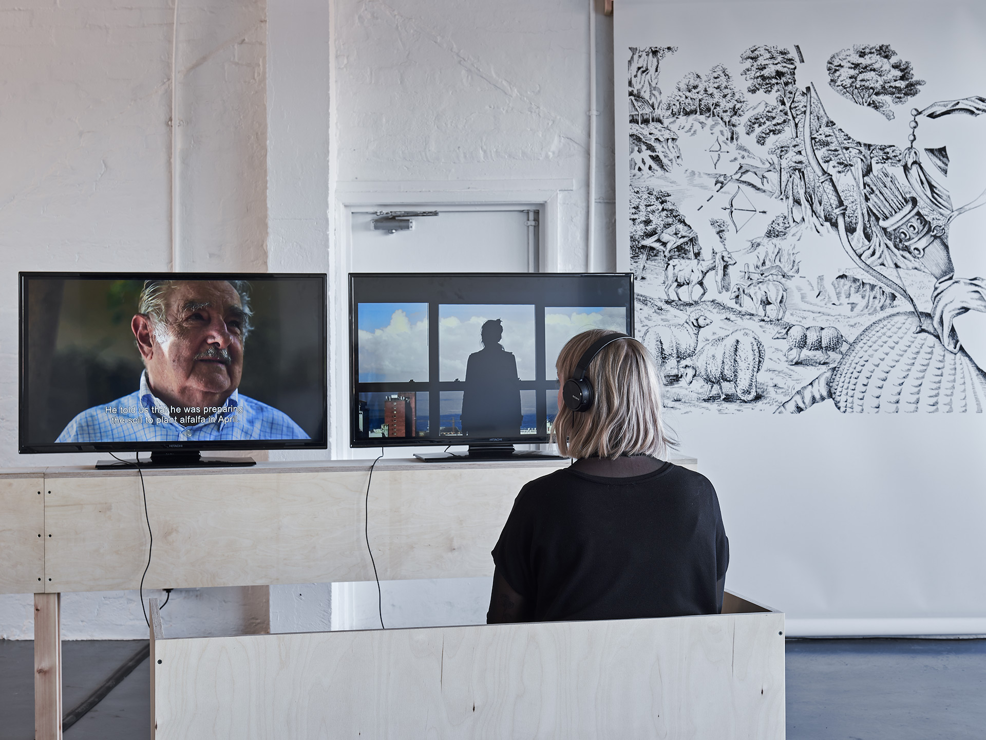 A person facing away wears headphones whilst watching a film on a TV. In the background the edge of a large drawing can be seen.