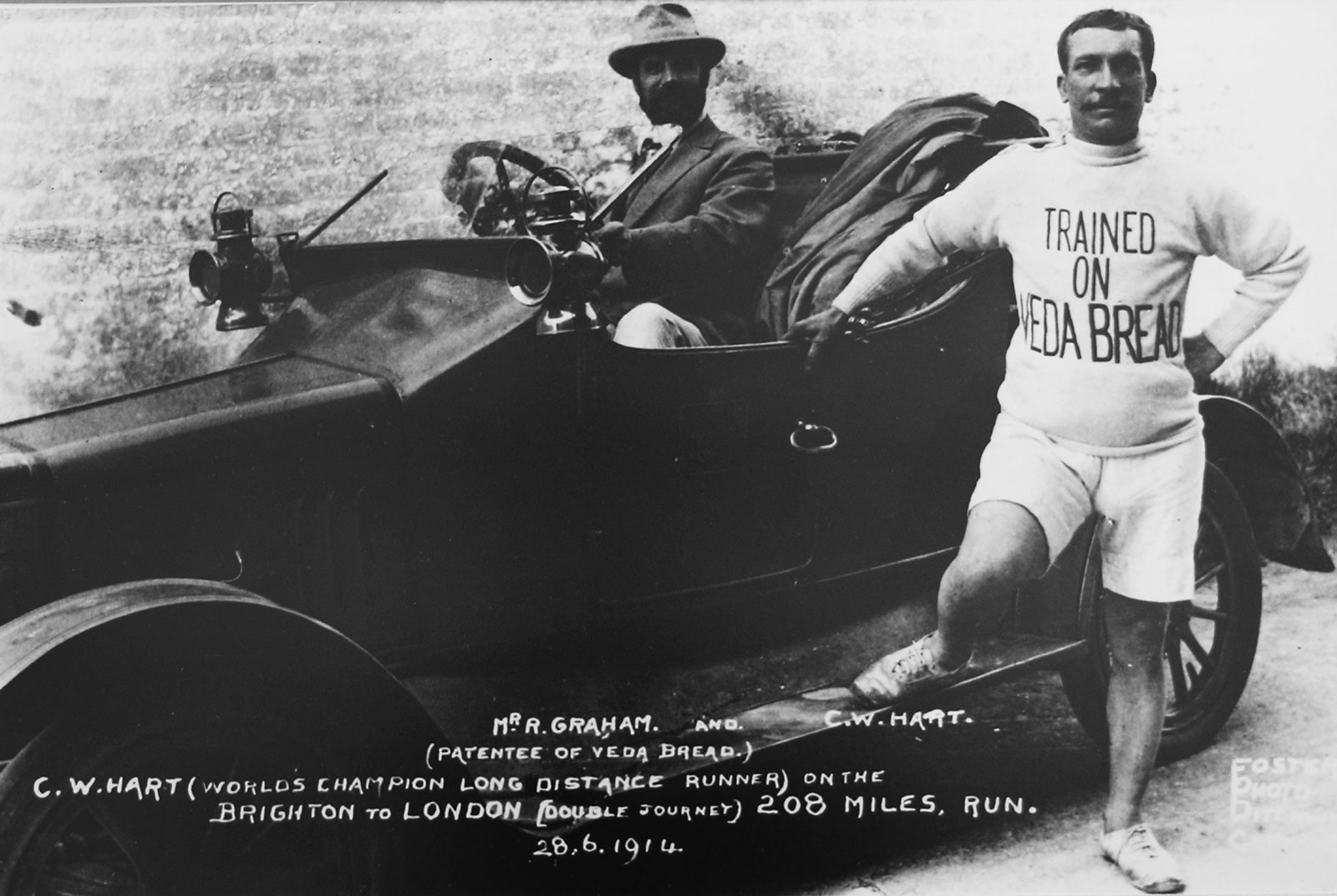 Black and White 1914 photo. An athlete leans on a vintage car, wearing a jumper that says Trained on Veda Bread.
