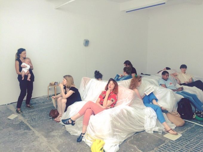 A group of people sit reading in the centre of a gallery space.