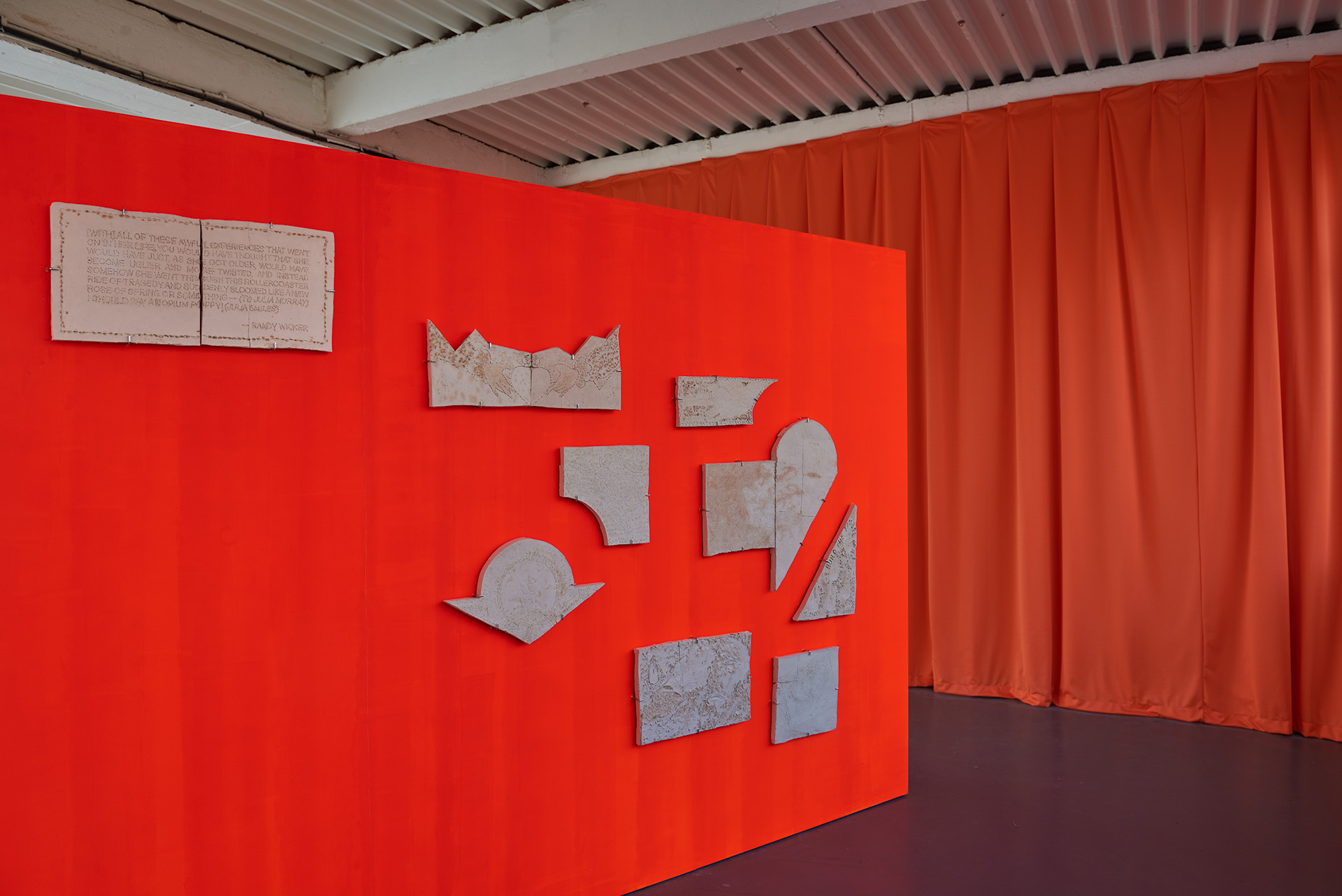 A series of fired ceramic slabs hung on a bright orange wall with a heavy orange curtain in the background.