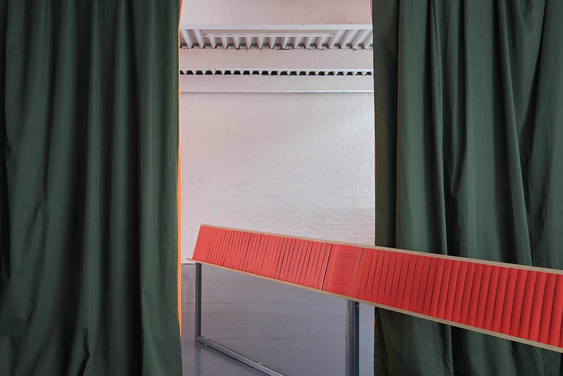 A custom made shelf, filled with red publications, cuts through a pair of heavy green curtains