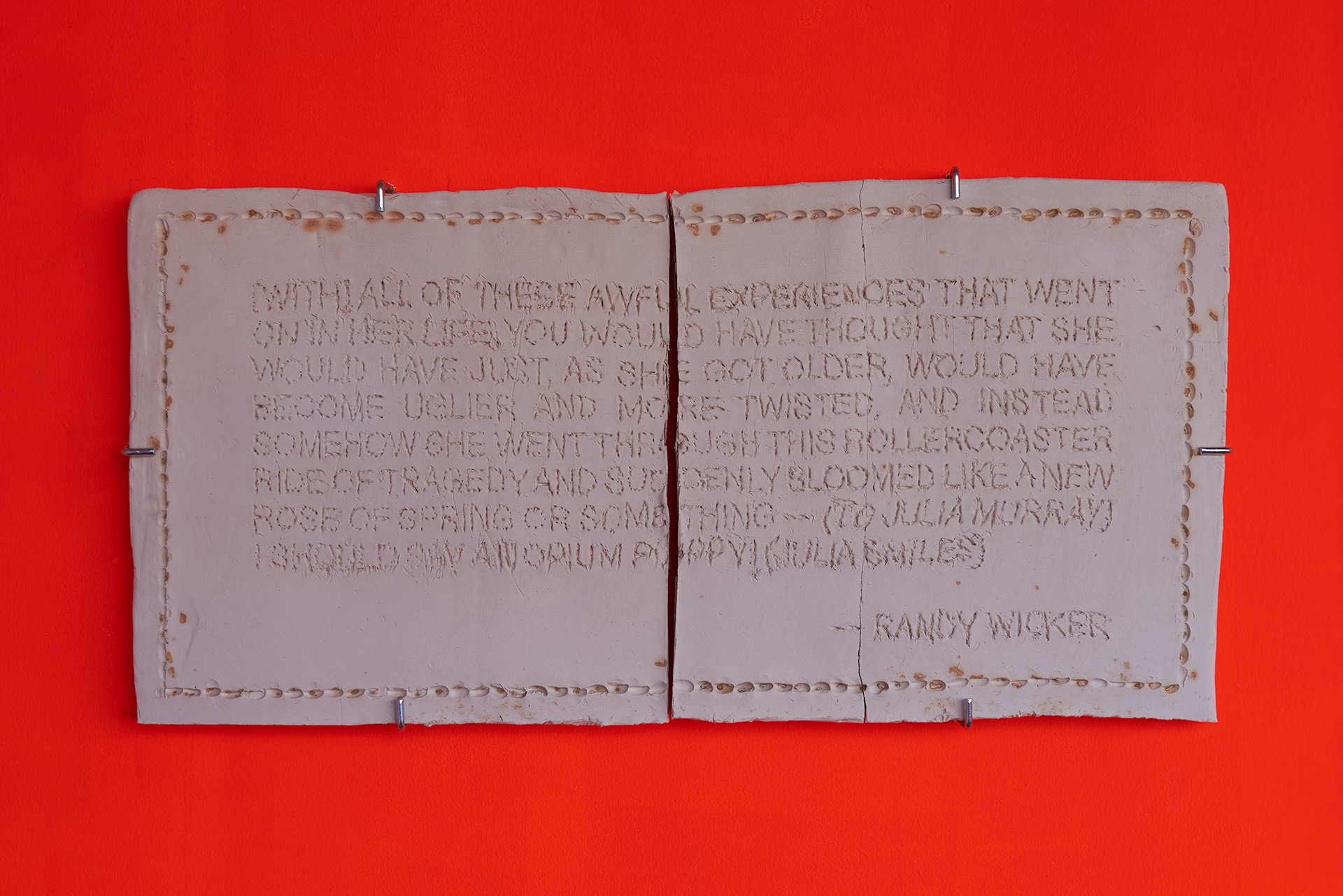 A fired ceramic slab inscribed with a quote by Randy Wicker on a bright orange wall.