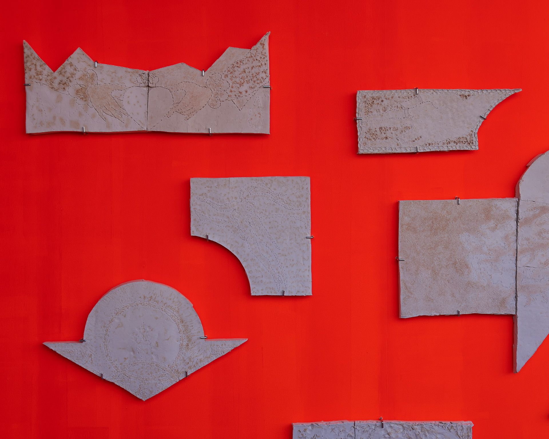 A series of fired ceramic slabs hung on a bright orange wall.