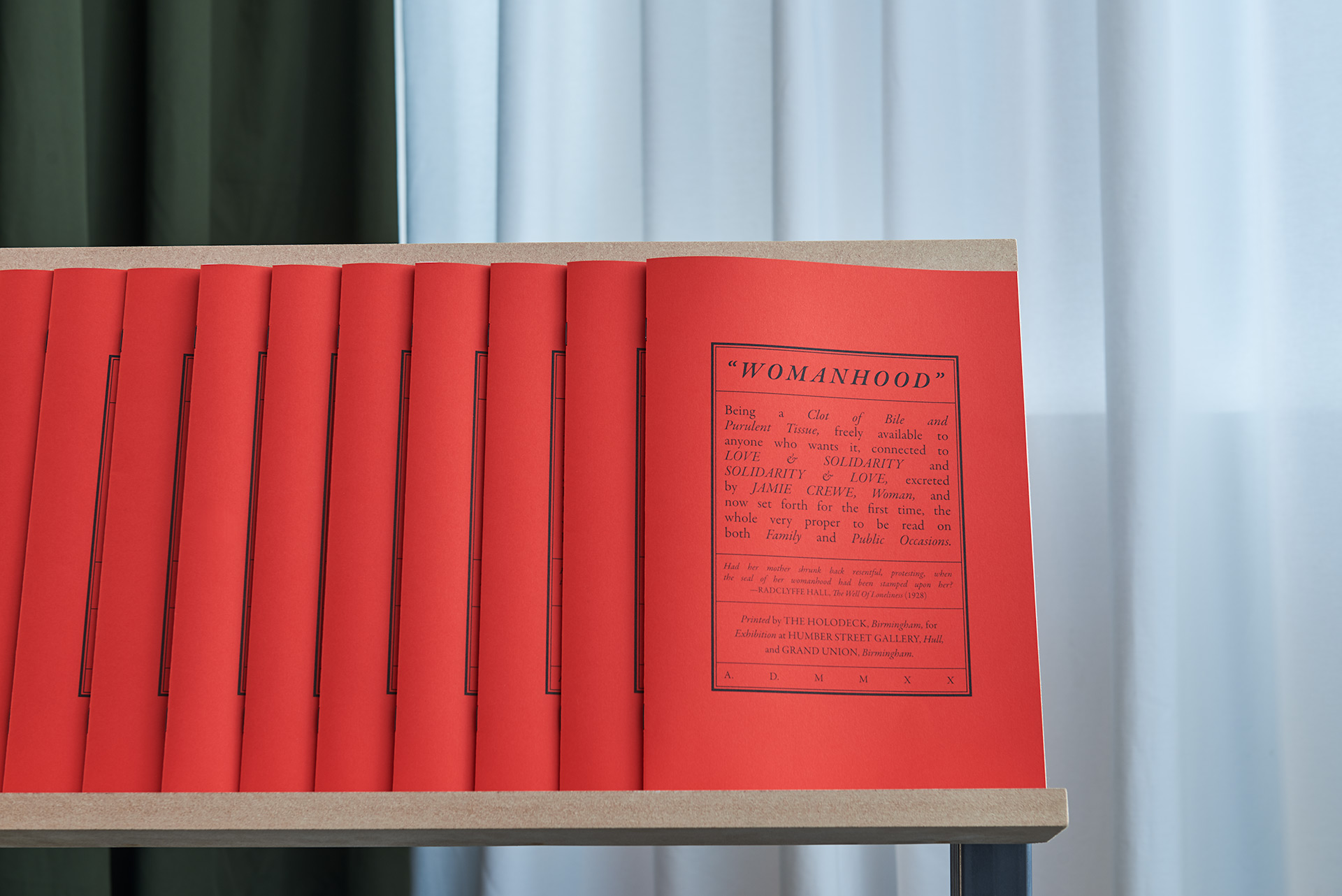 A custom made shelf, filled with red publications with green and white curtains in the background.