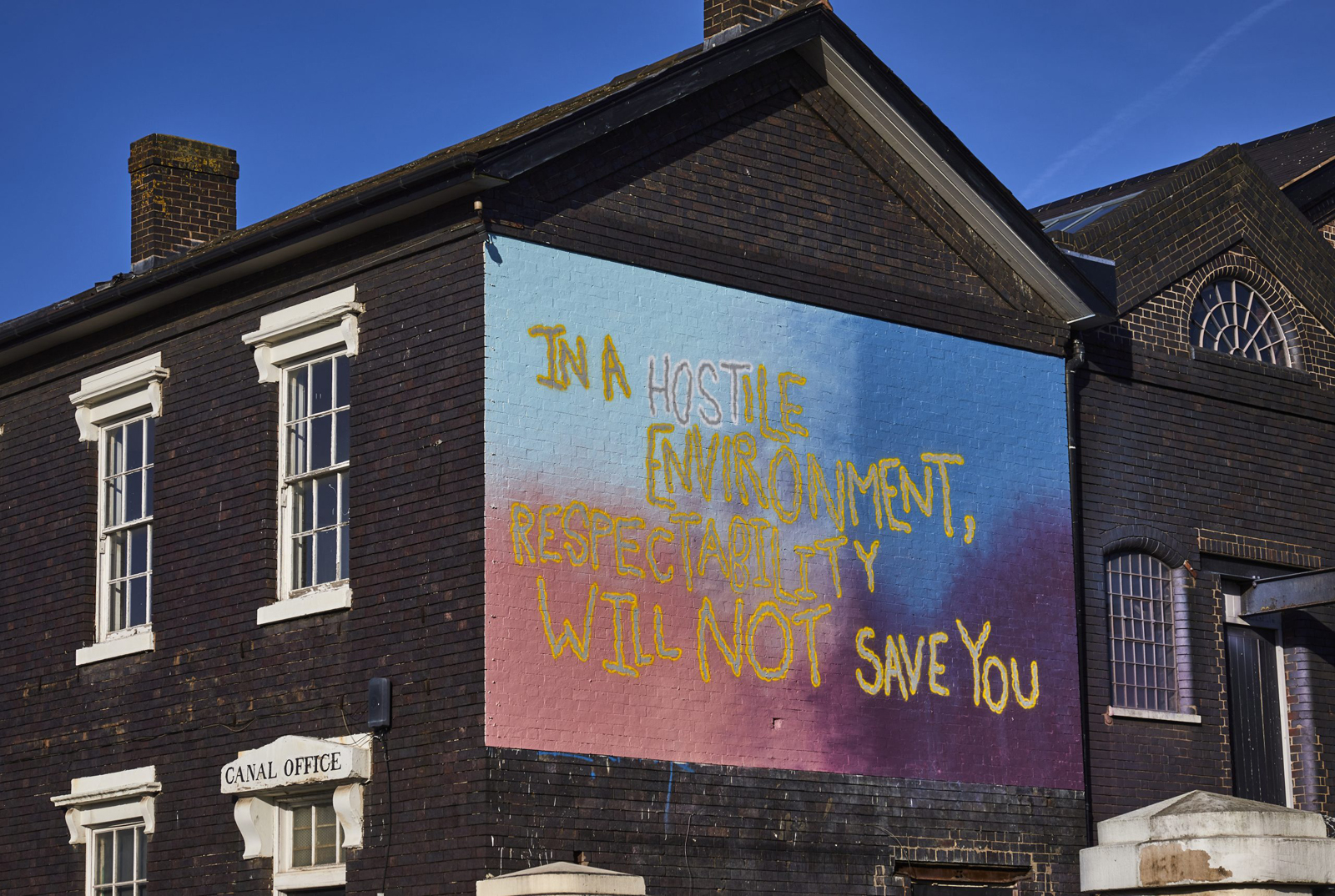 A sign painted on the side of Junction Works building. In yellow and white it reads, In a hostile environment respectability will not save you.