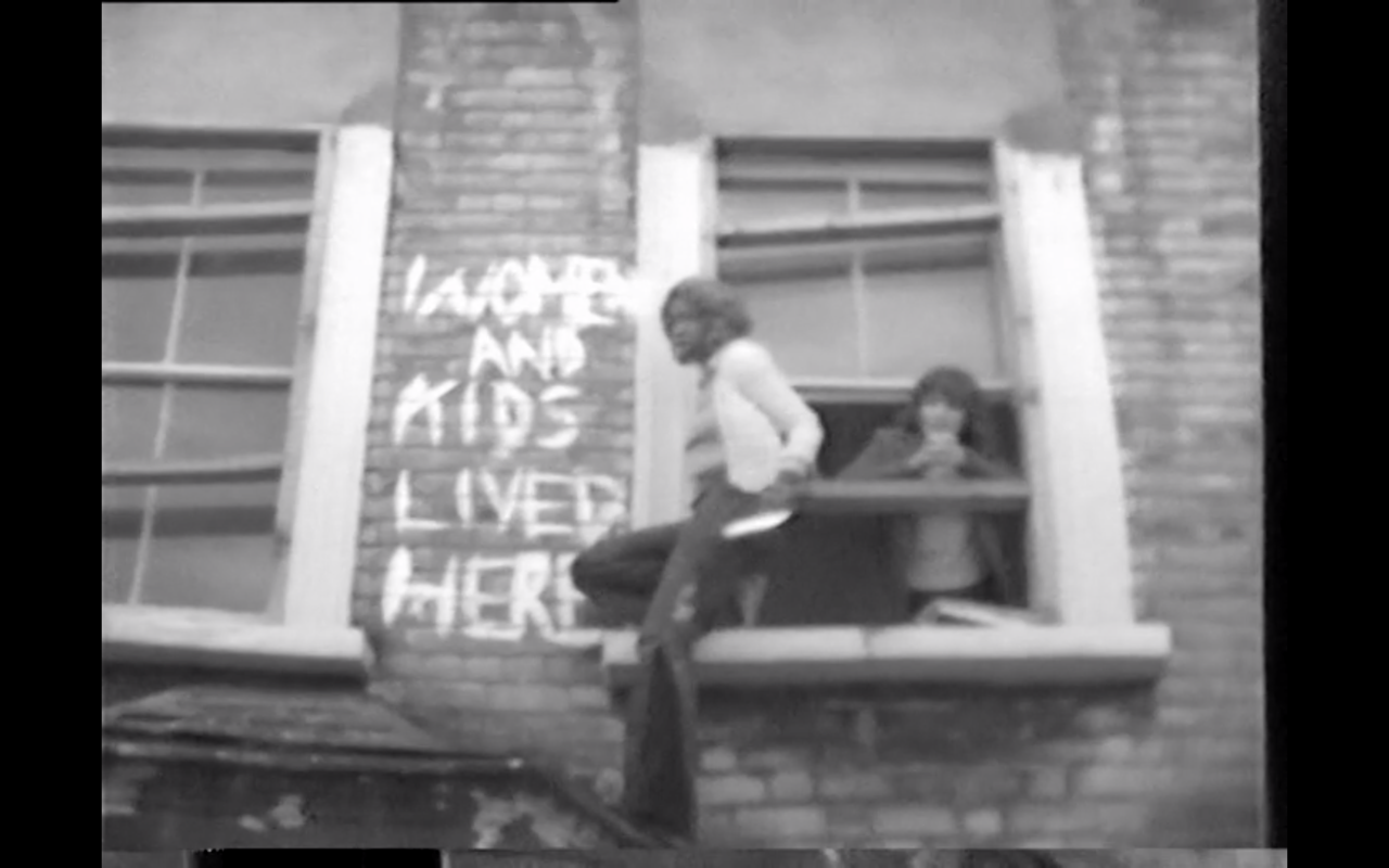 A person climbs out of a decrepit window. 'Women and kids lived here' is painted on the wall behind them.